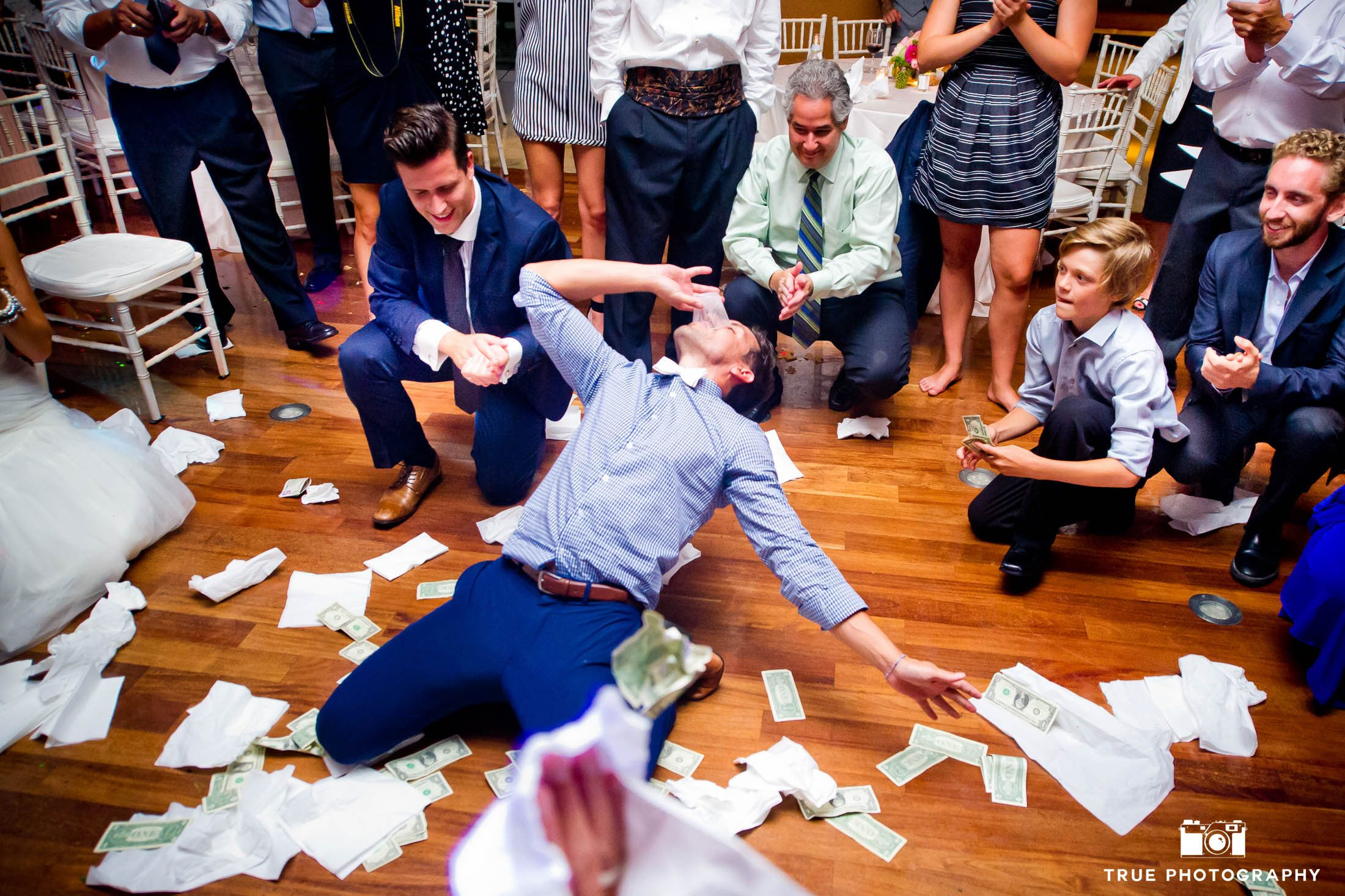 Groom takes shot and has money throw at him during wedding reception
