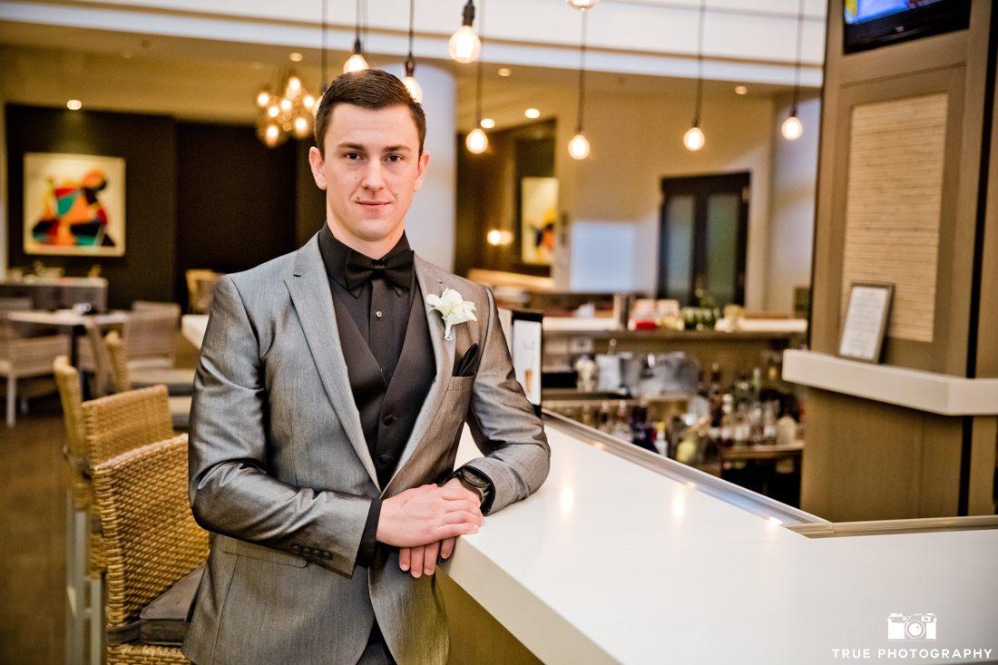 Portrait of groom in grey suit and black tie