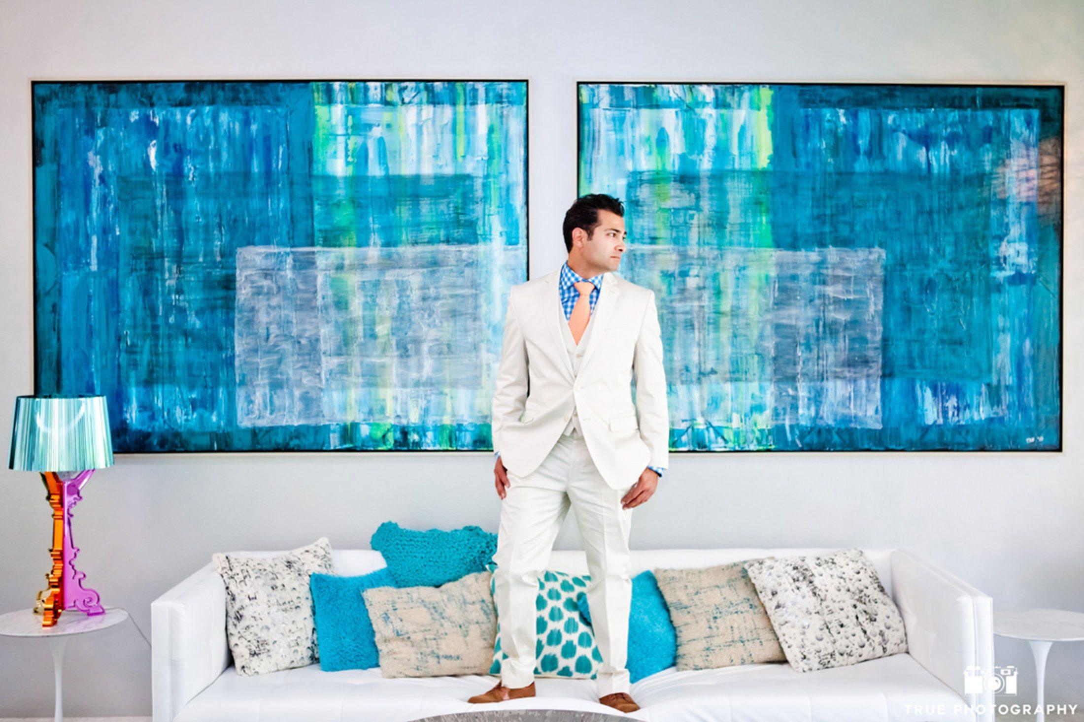 stylized portrait of groom wearing a white suit
