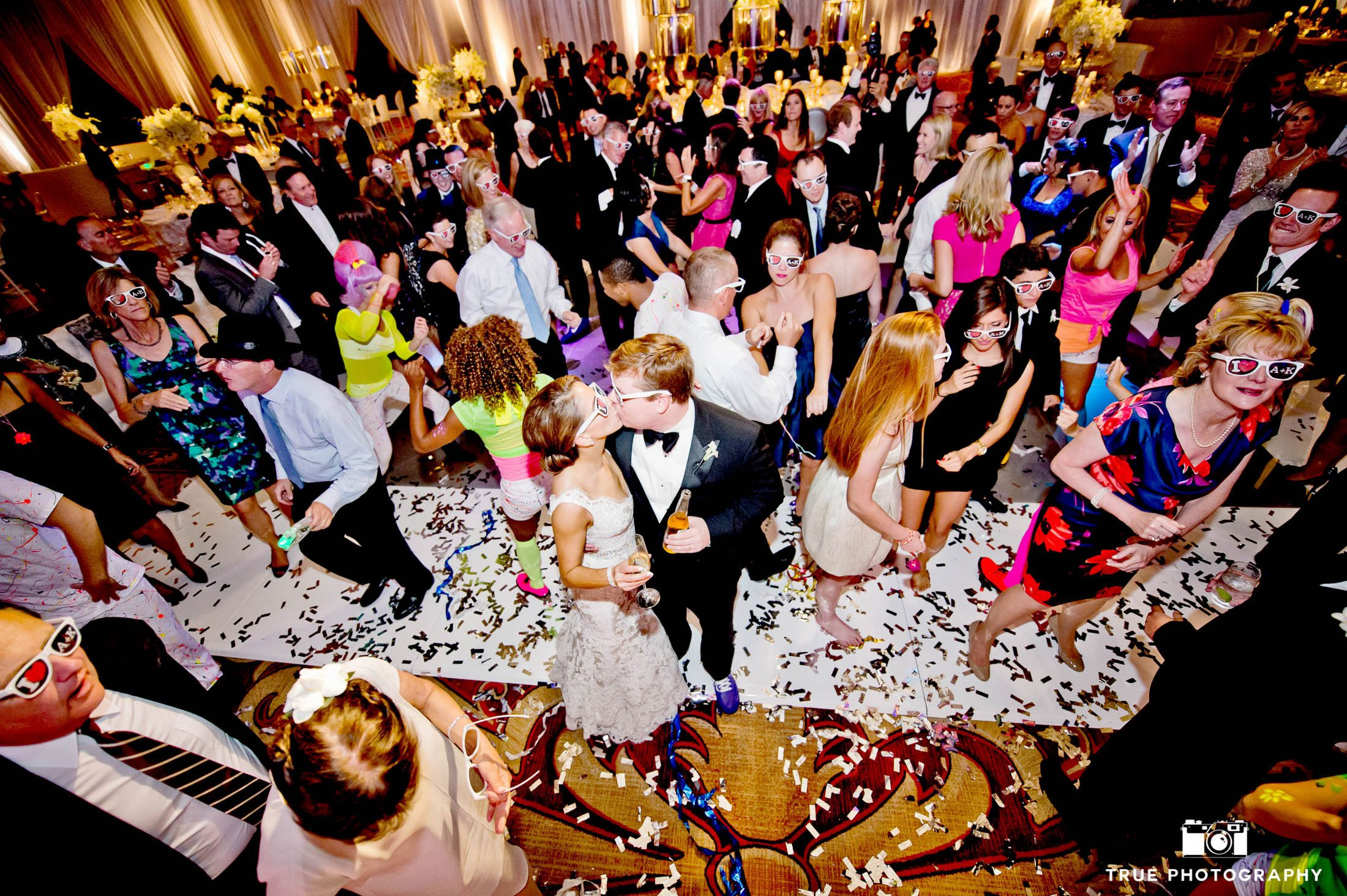 Bride and Groom stand in crowd and kiss during wedding reception