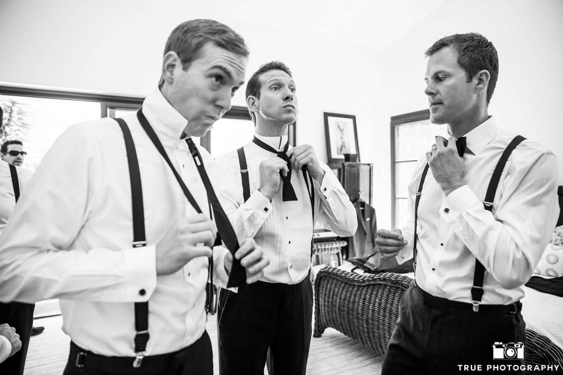 Groomsmen with style putting on bowties