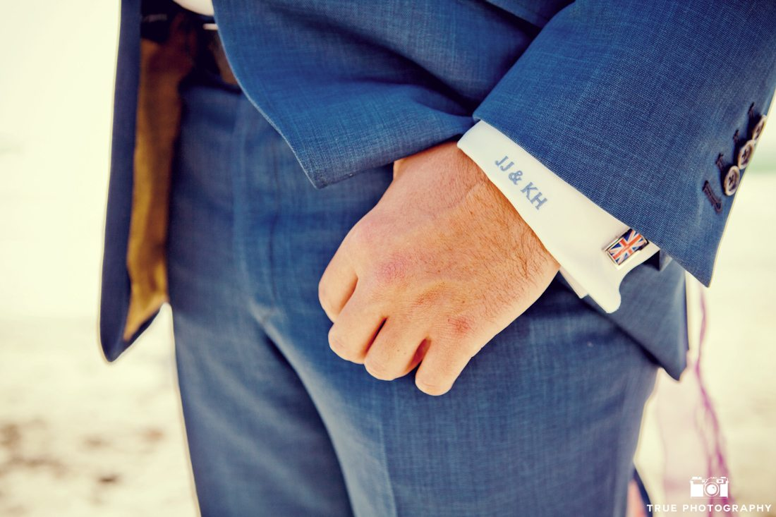 Close-up of groom wearing cuff links and and monogrammed dress shirt