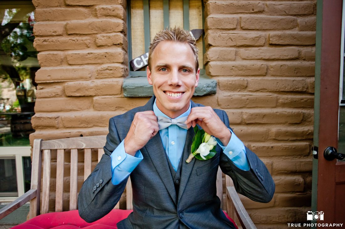 Portrait of Happy Groom holding bowtie