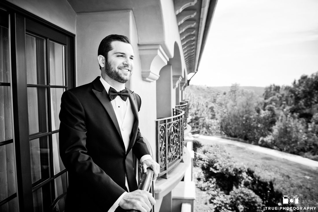 Groom on a balcony at the Fairmont Grand Del Mar wearing a classic black tuxedo