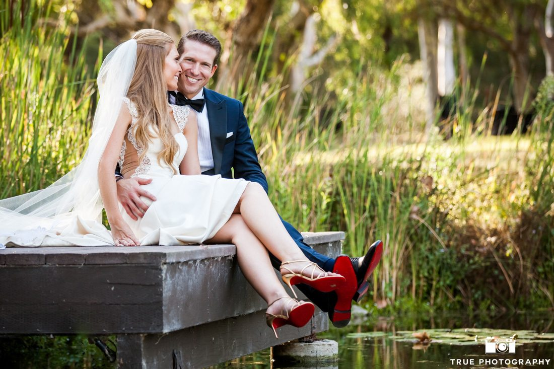 Bride and groom wearing Louboutin shoes sitting at the edge of dock