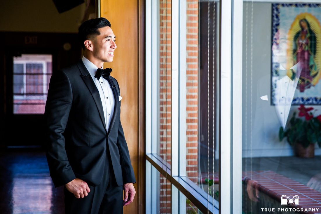 Groom in Stylish black tuxedo looking out the window for his bride