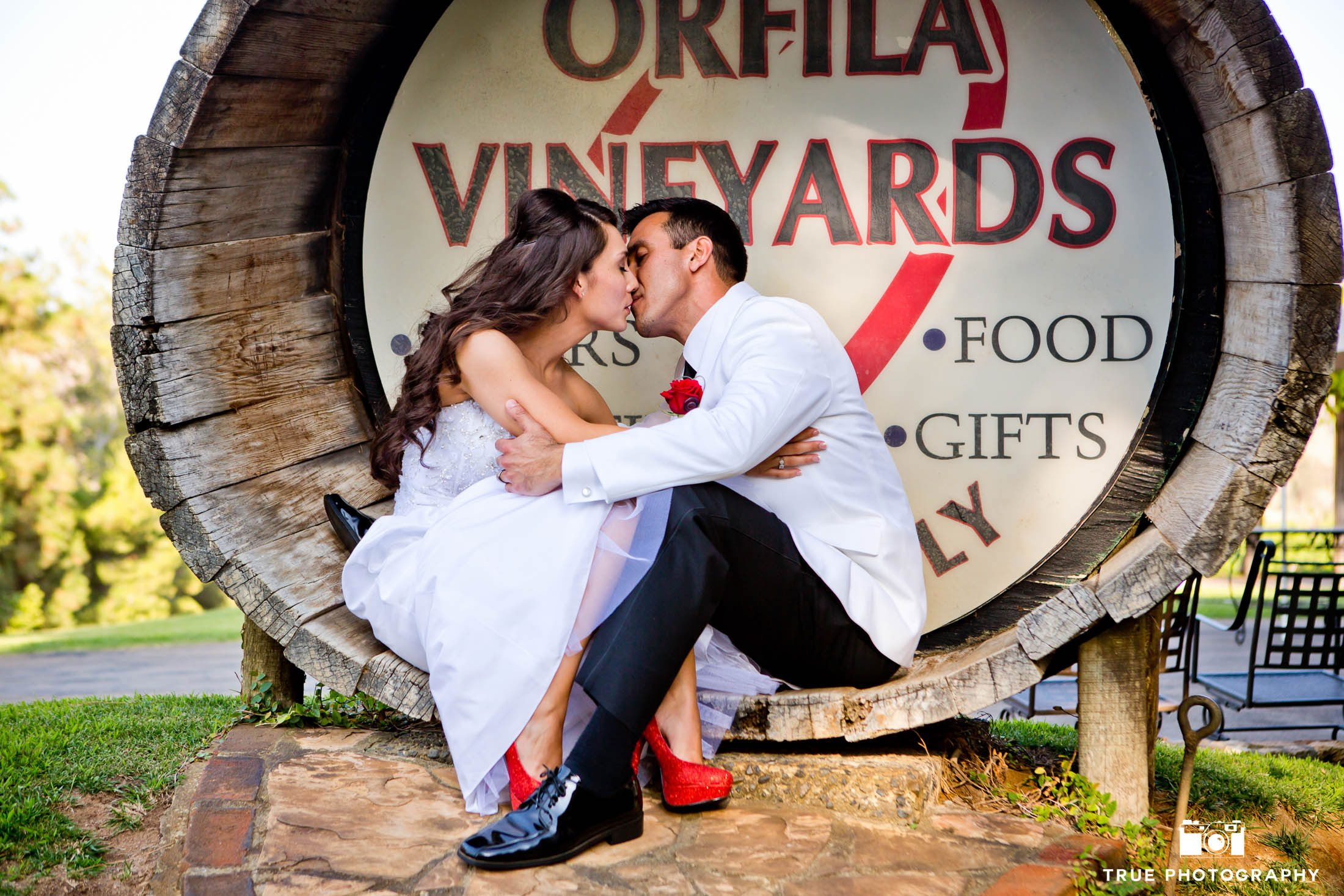 Couple kiss in oversized wine barrel