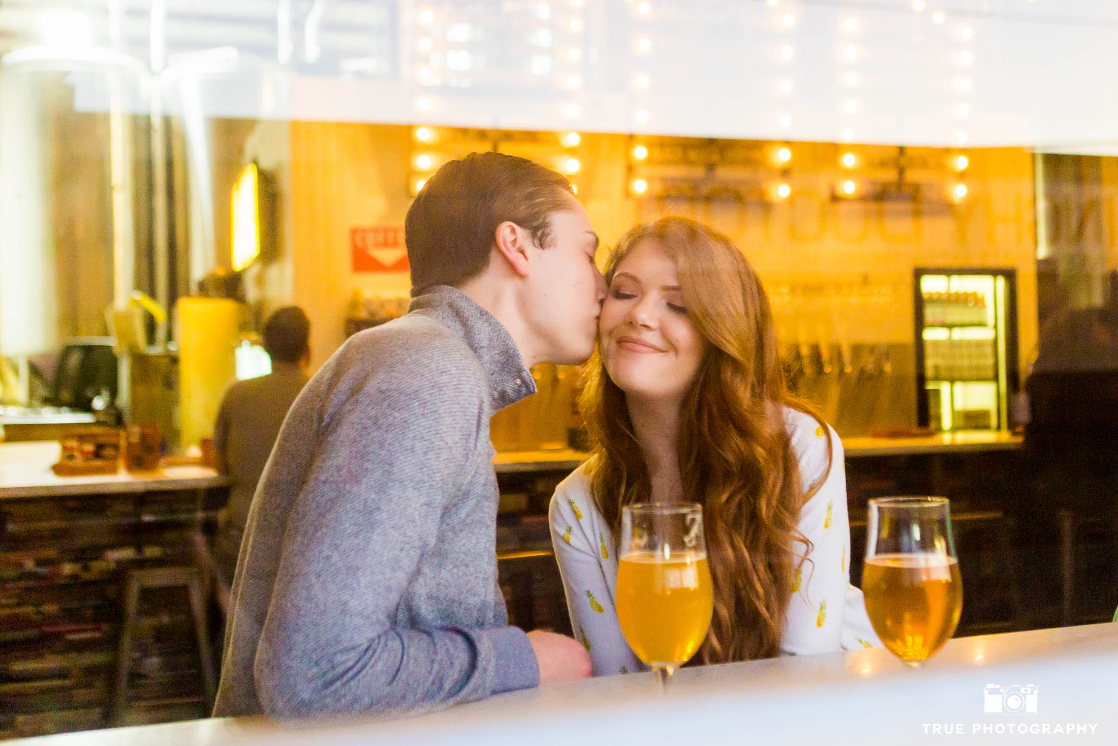 couple enjoying craft beer at Modern Times Brewery at their engagement photo shoot