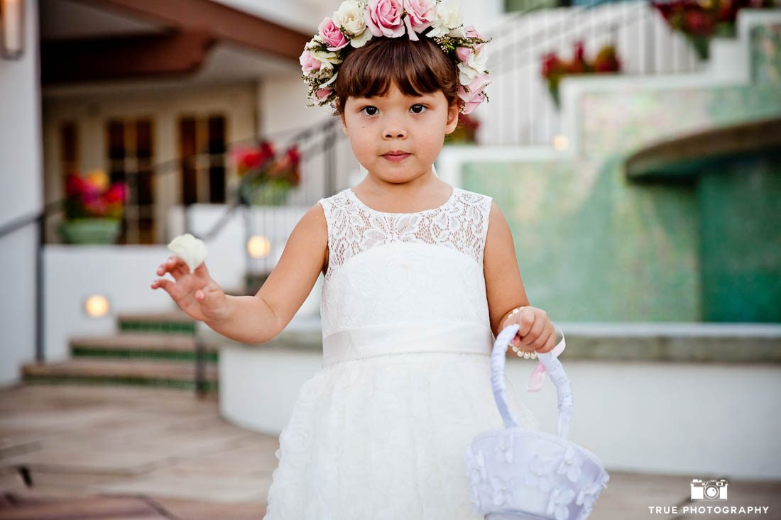 A flower girl walks down the aisle in a rose flower crown