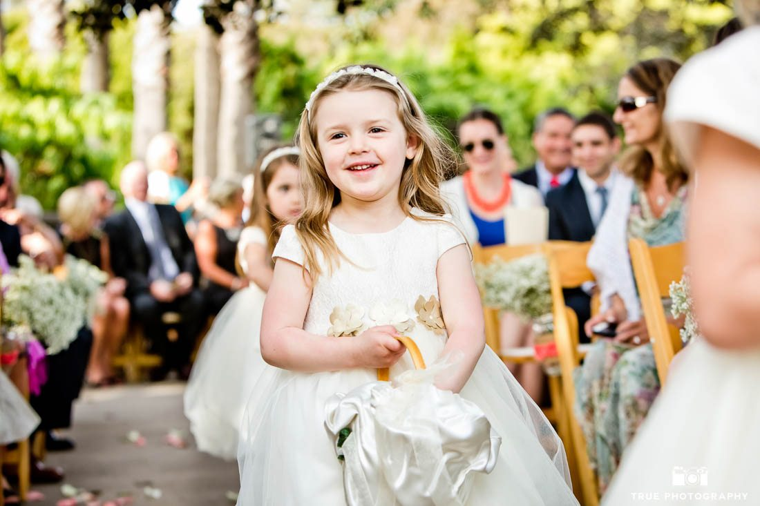 Flower girl walks down the aisle in neutral tones