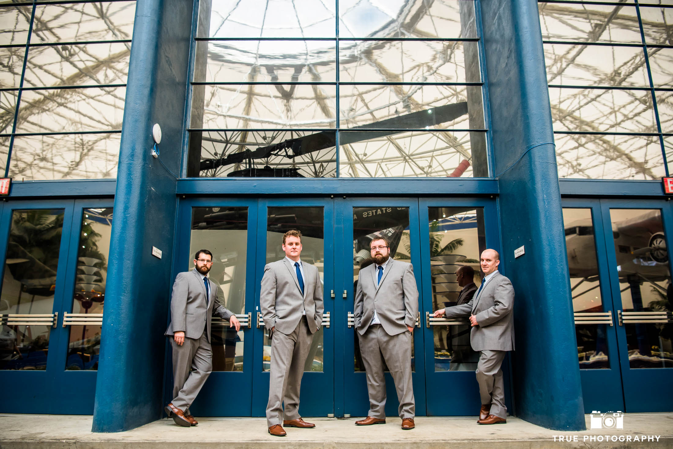 Groom and Groomsmen stand in front of blue doors at San Diego Air and Space Museum