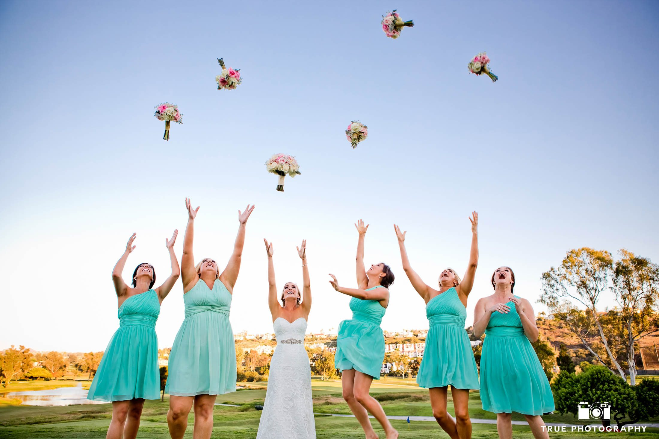 Bridesmaids and Bride toss wedding bouquets up in air