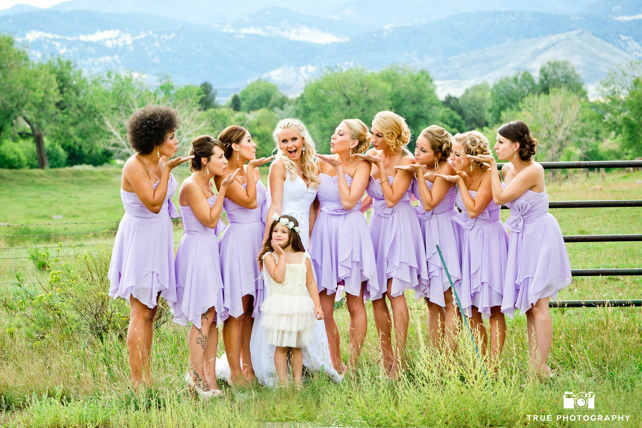 Bridesmaids blow kiss towards bride