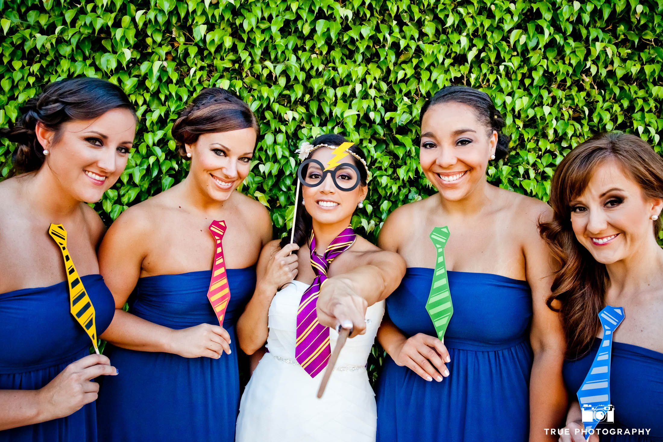 Bridesmaids pose with Bride as they wear Harry Potter props