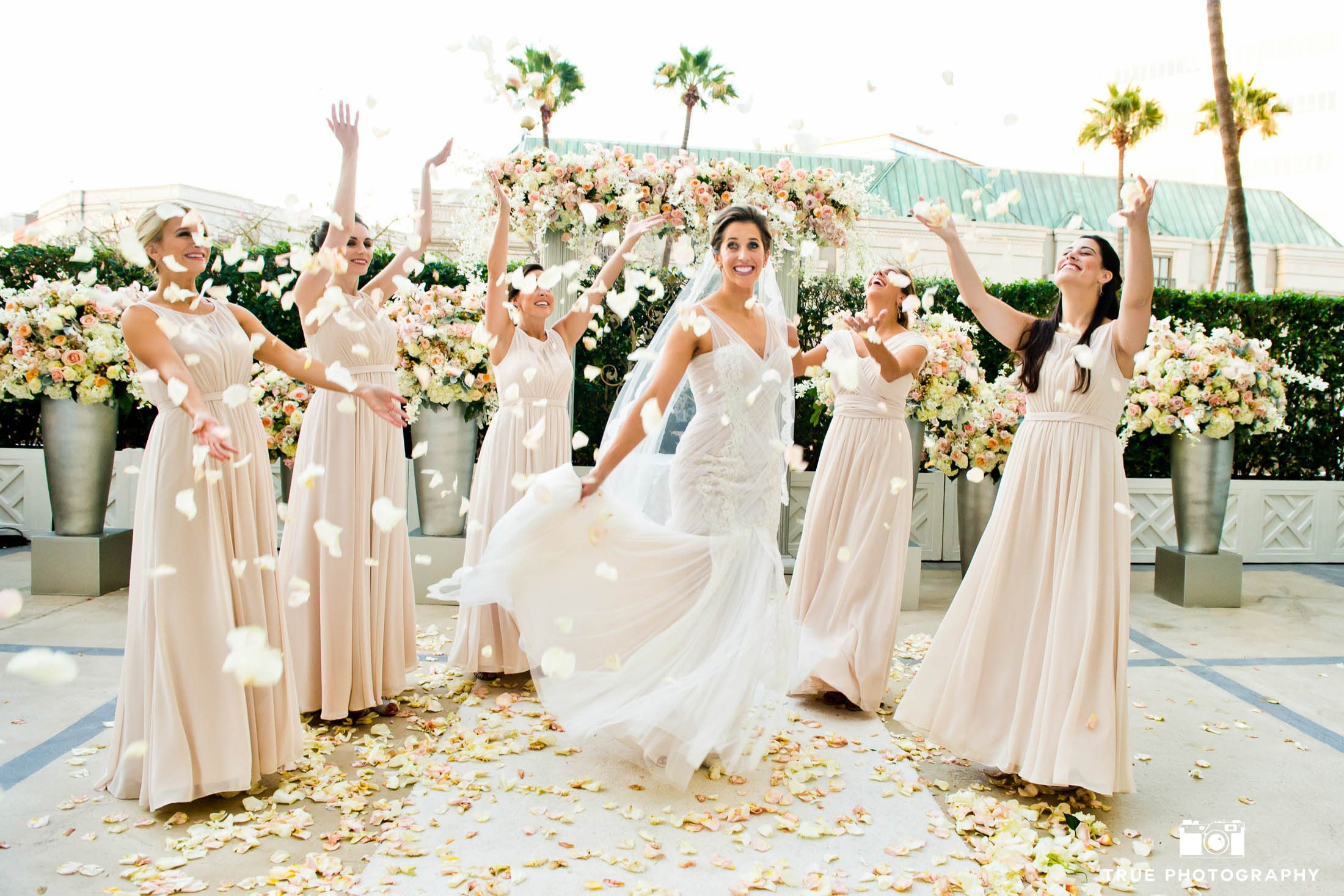 Bridesmaids throw rose petals around Bride after ceremony
