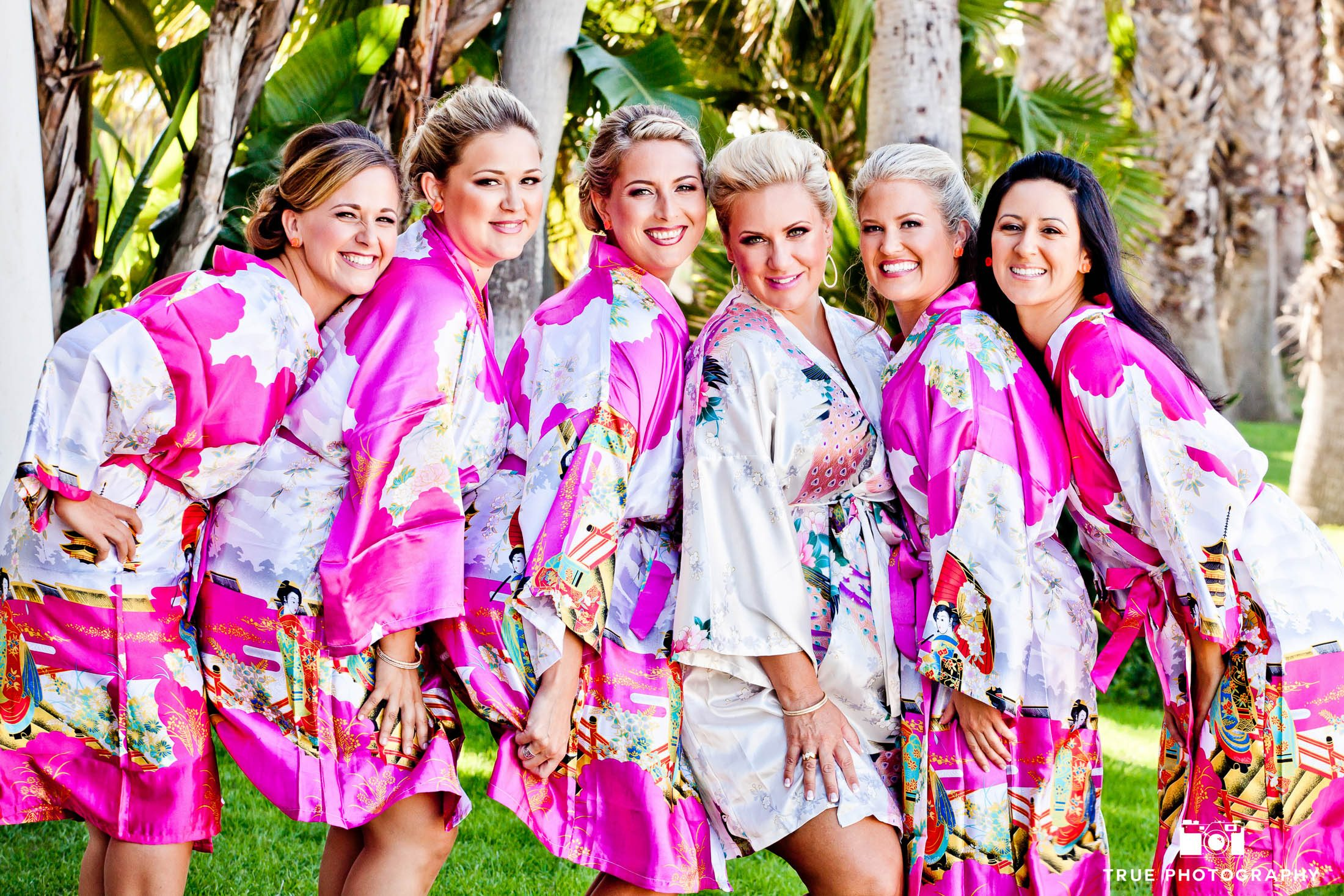 Bride and bridesmaids pose with pink robes before wedding ceremony