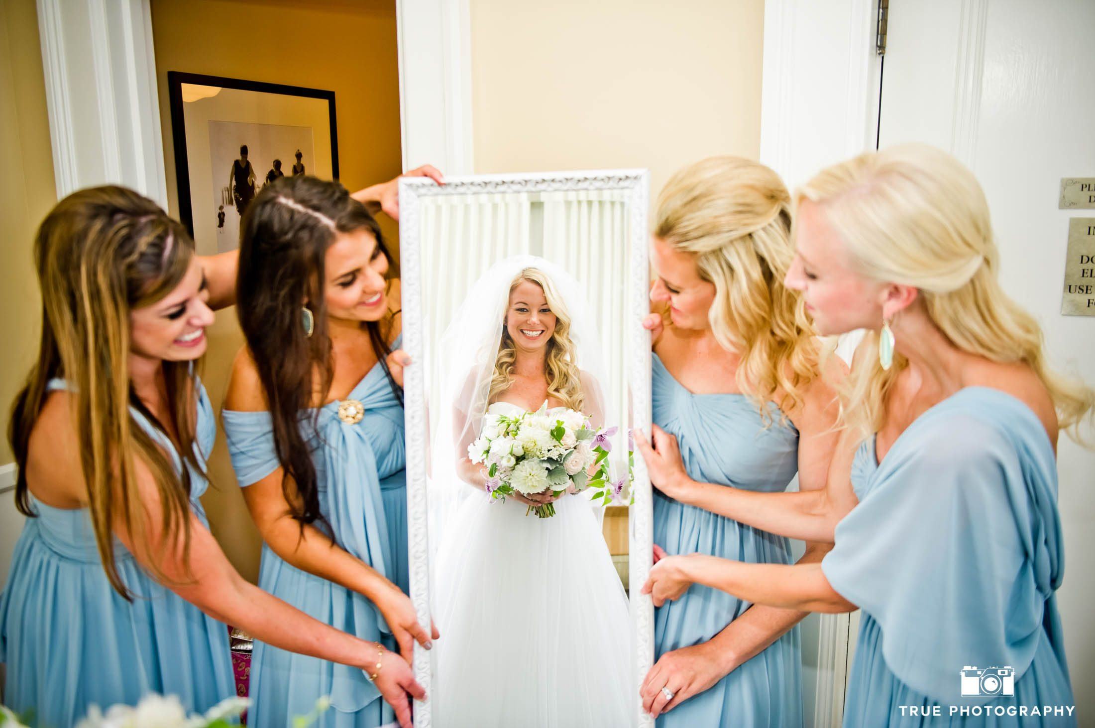 Bridesmaids hold up mirror for Bride to reveal herself