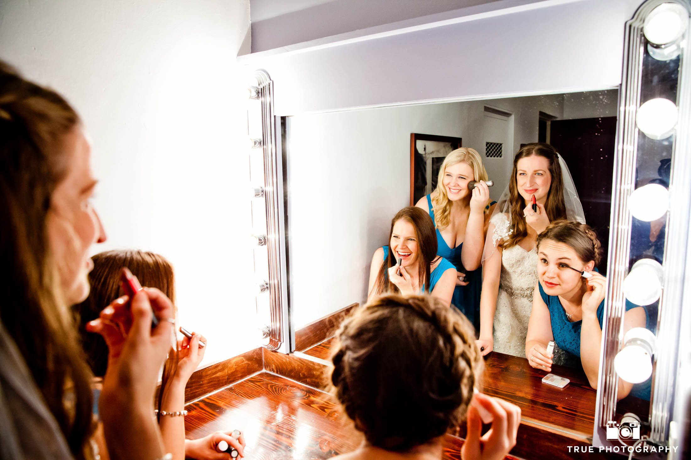 Bridesmaids share mirror with bride on wedding day
