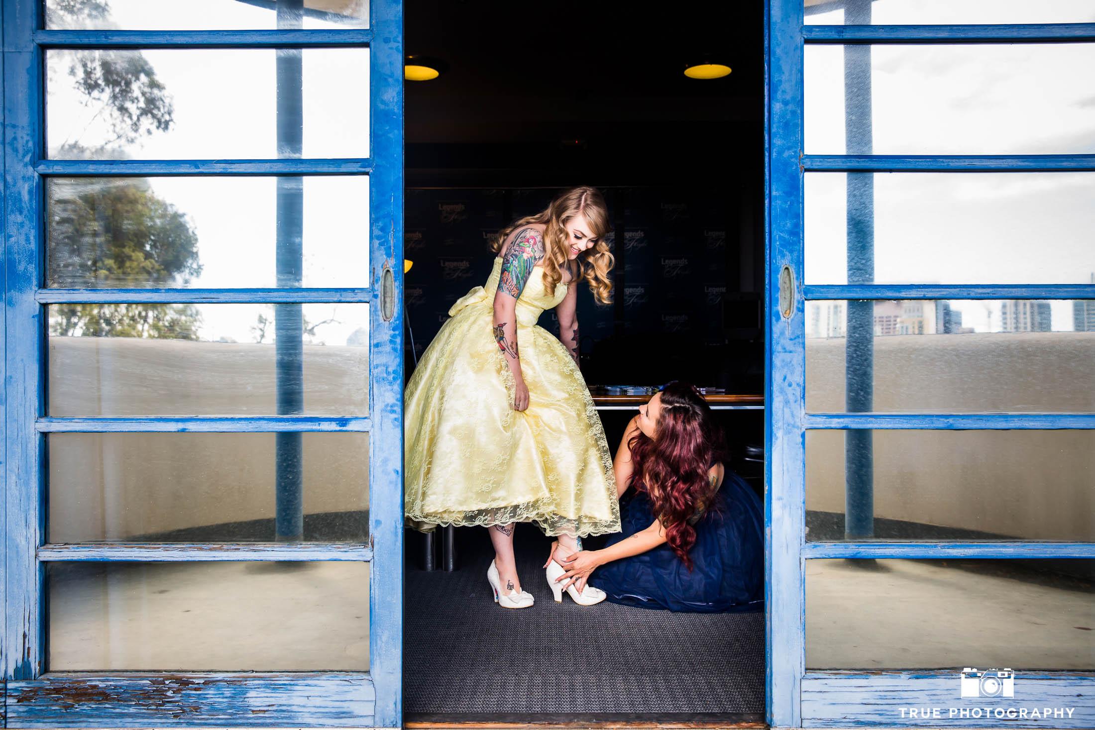 Bridesmaid helps Bride put on shoe before wedding ceremony