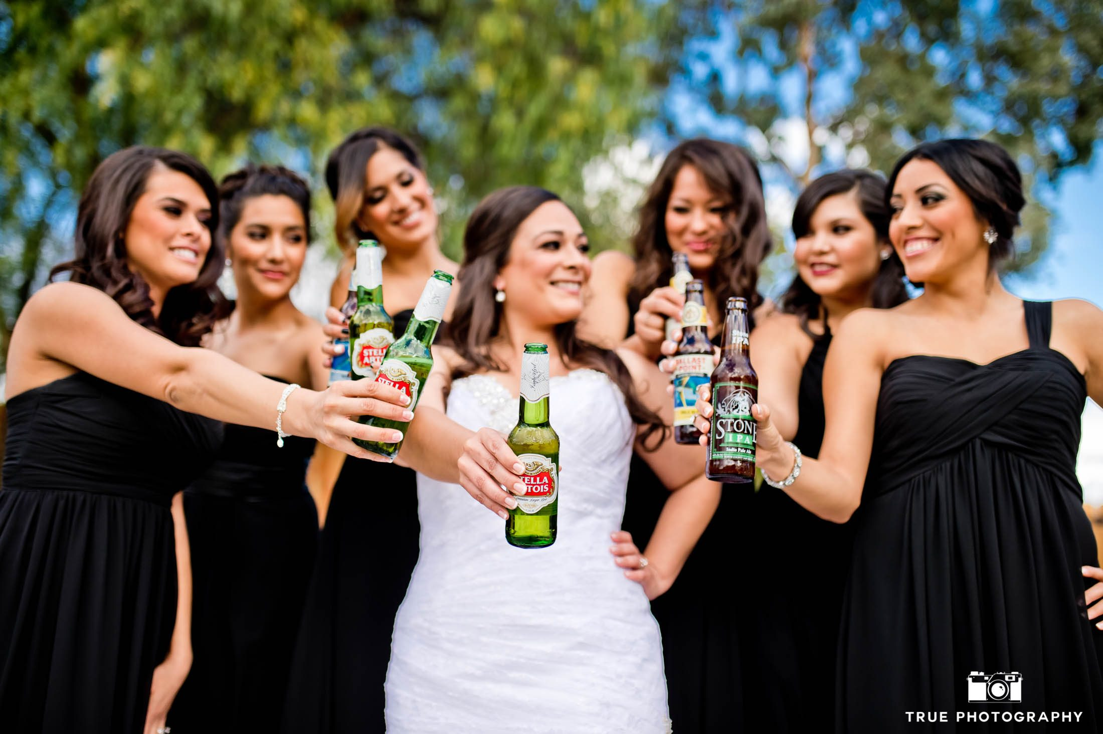 Bride and bridesmaids toast with craft beers