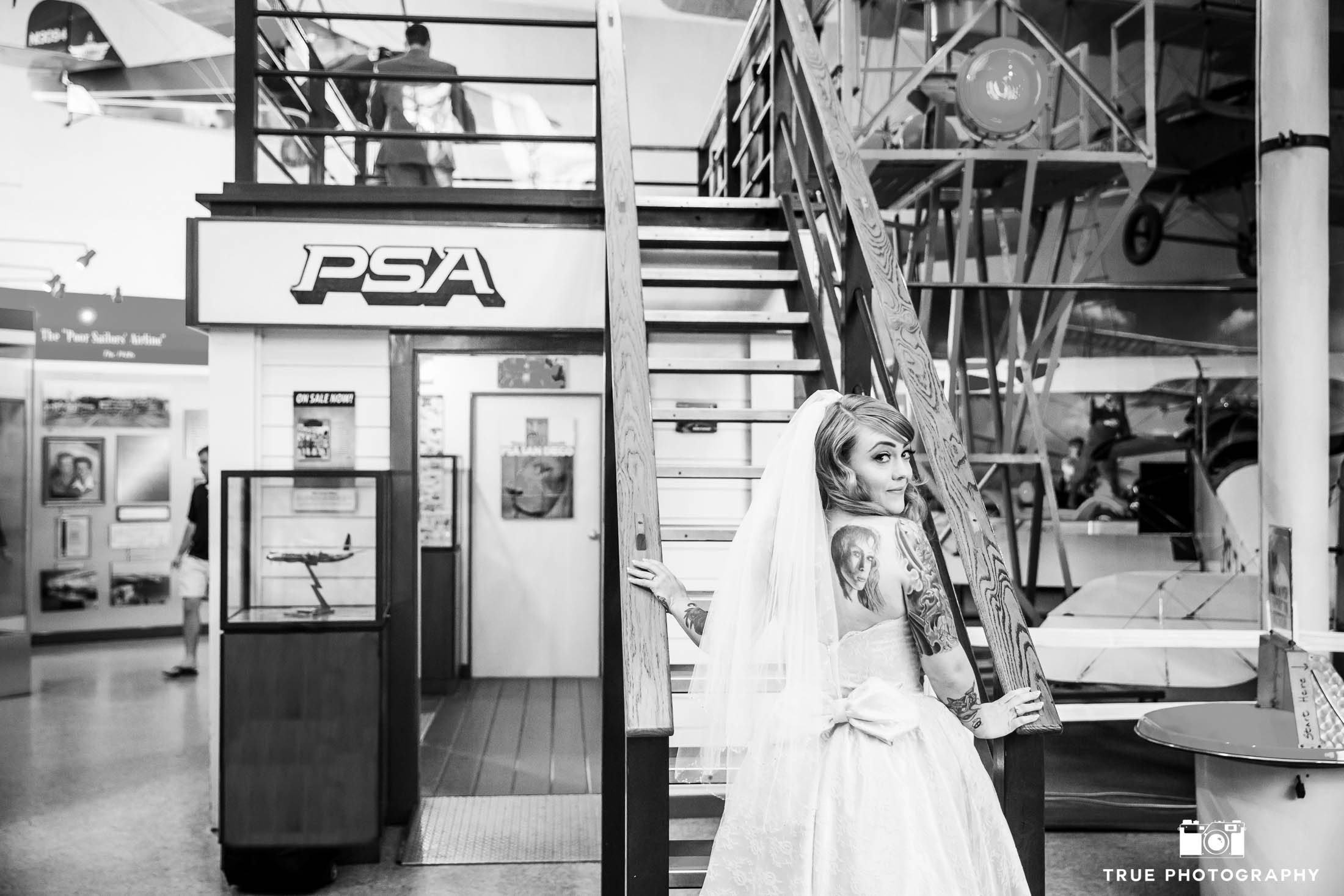 Bride climbs stairs up to Groom for First Look inside Air and Space Museum