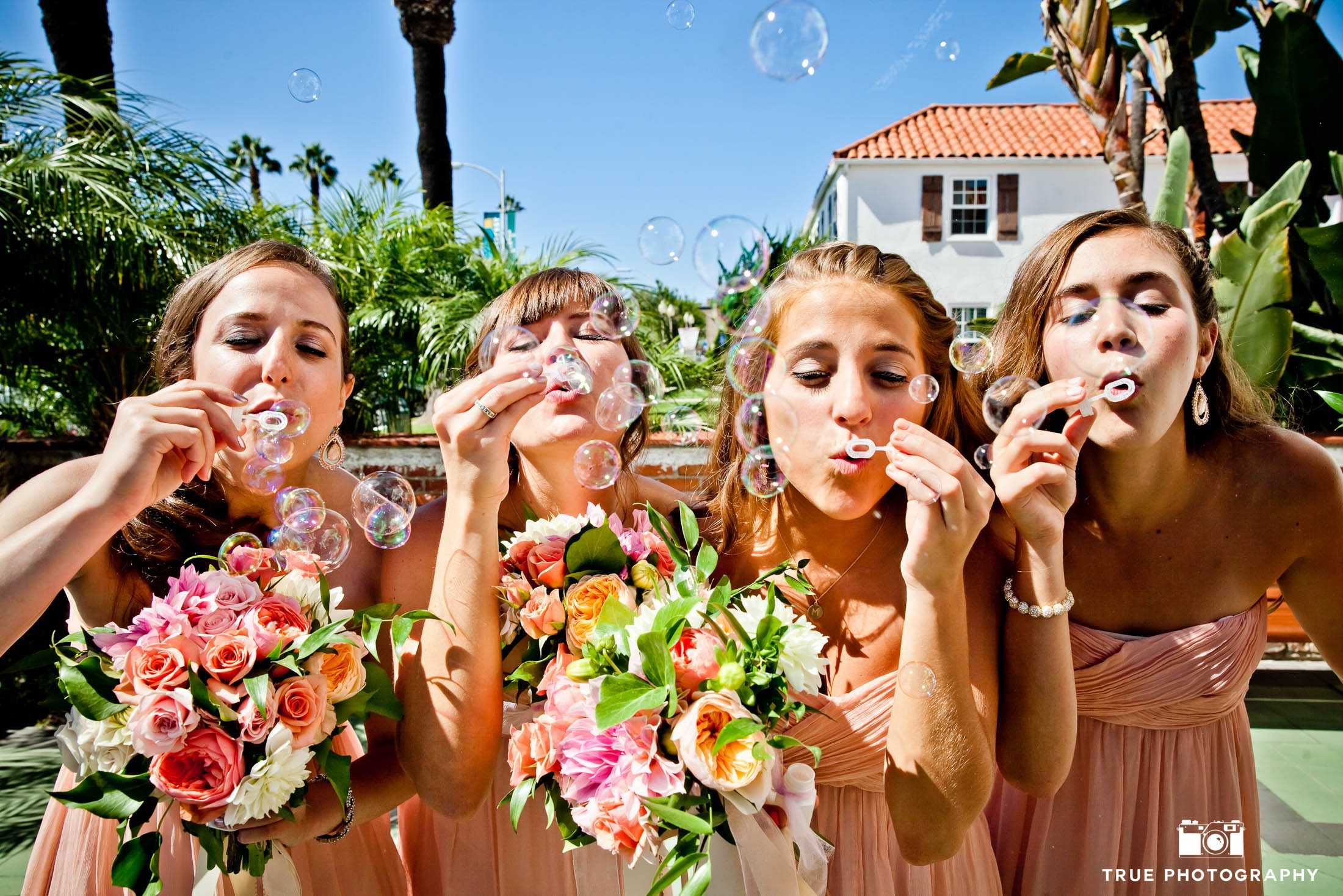 Bridesmaids blow bubbles at camera before wedding ceremony