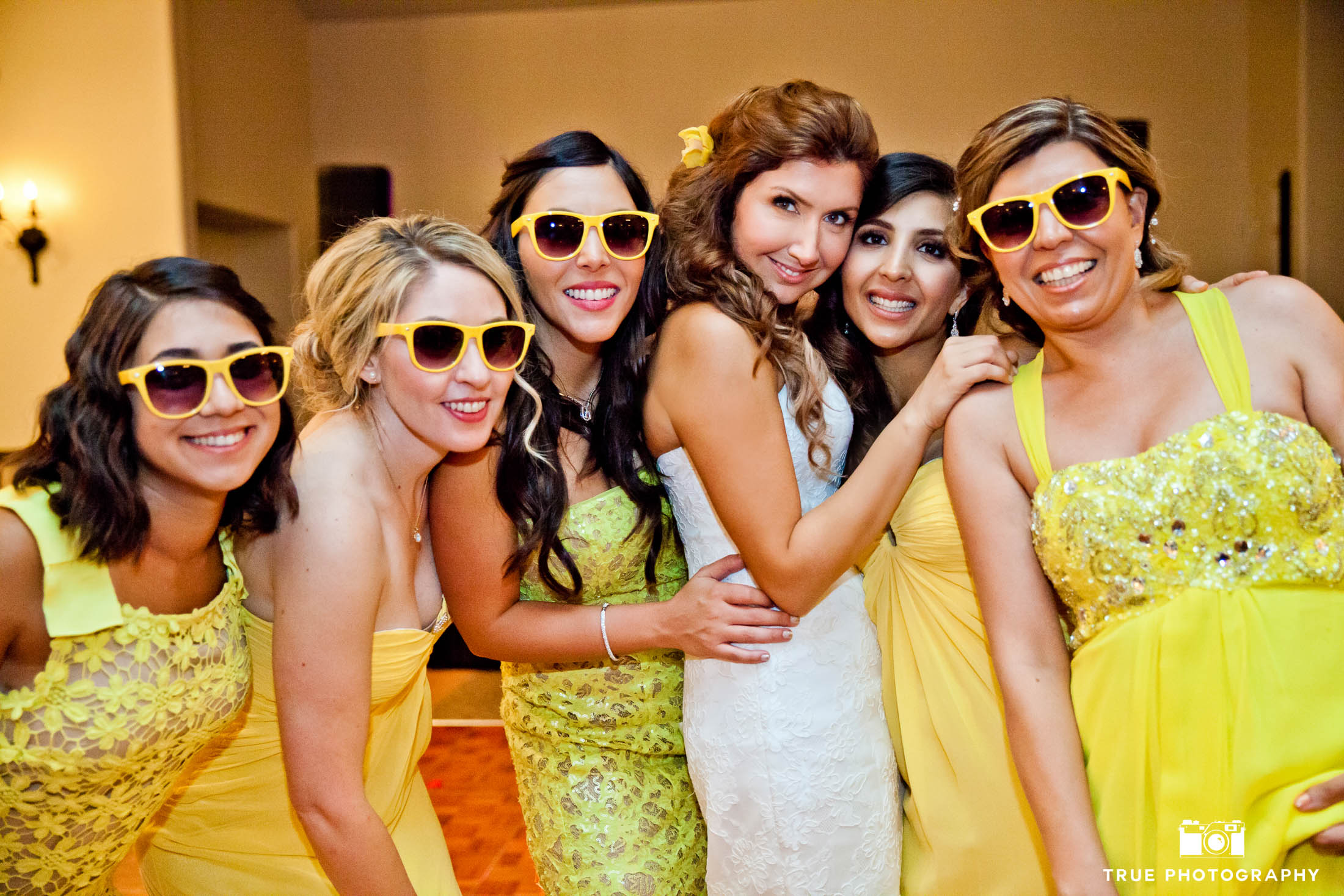 Bridesmaids pose with Bride and wear yellow sunglasses
