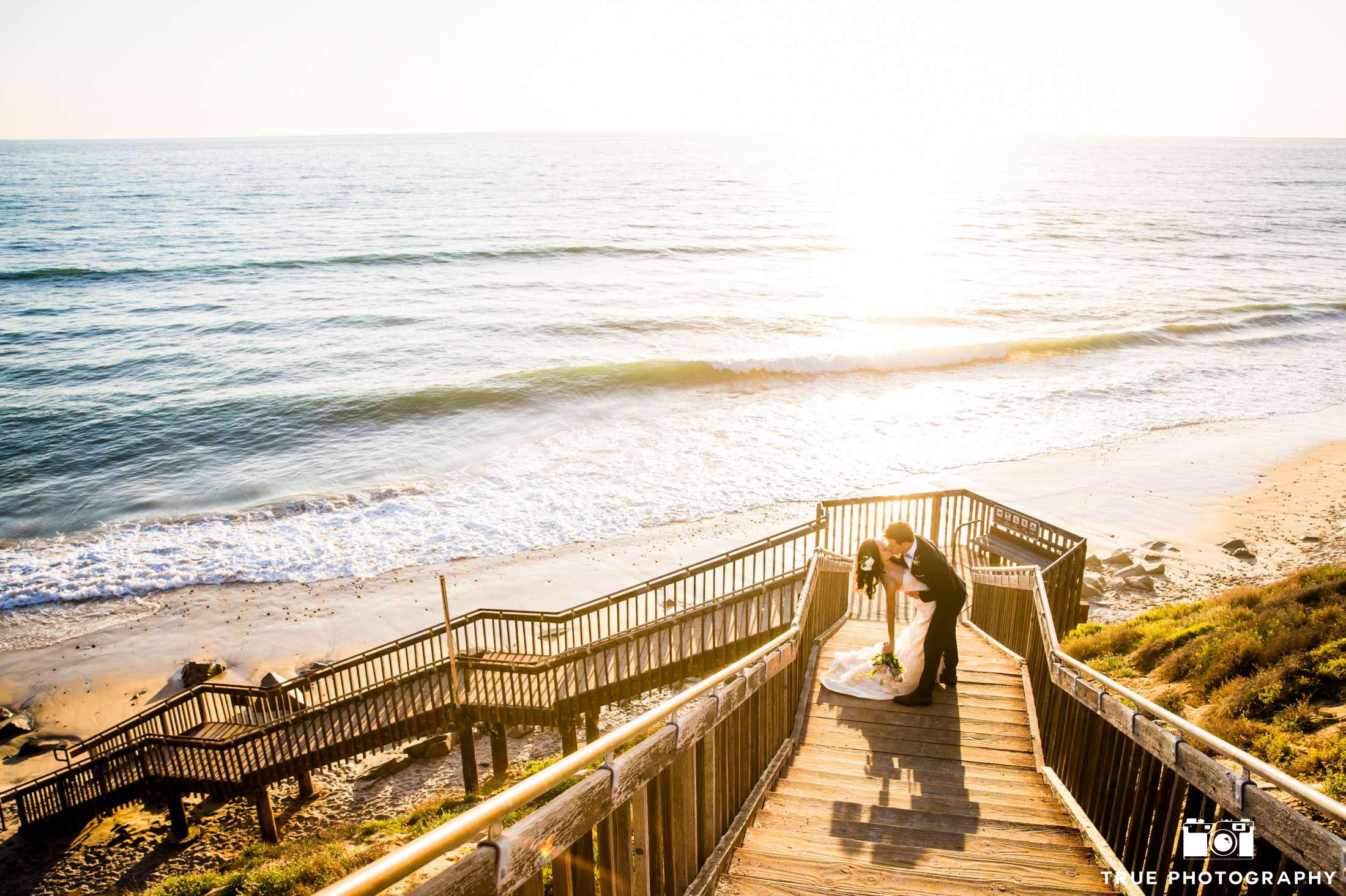 Cape Rey Hilton couple kissing on the stairs at Carlsbad beach