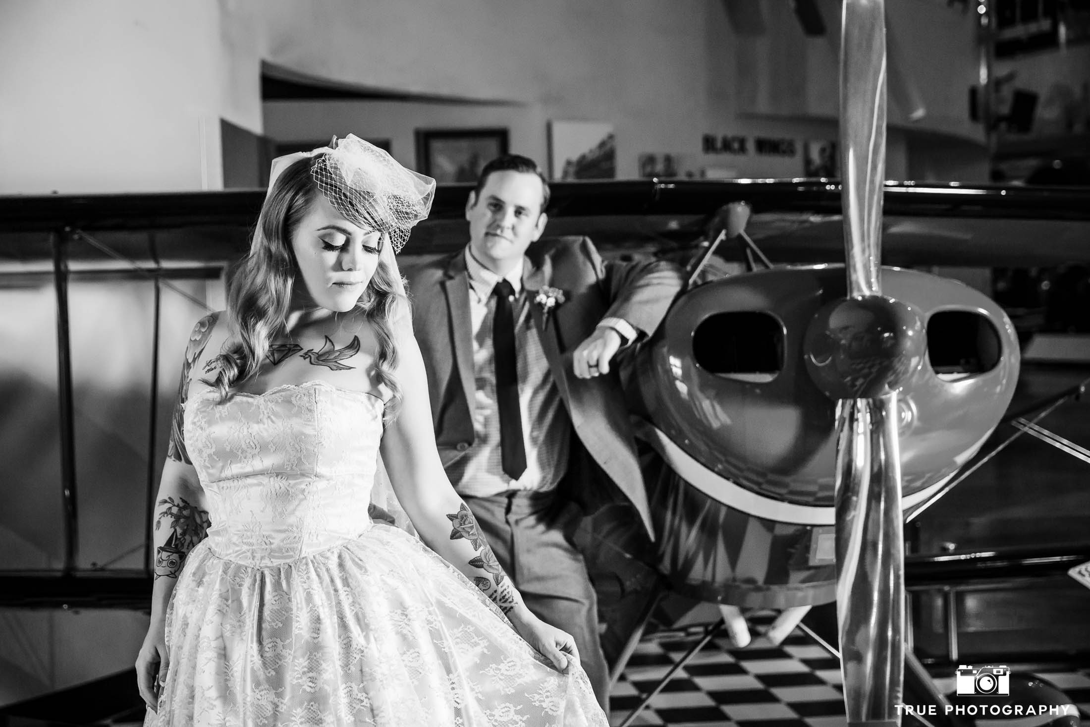 Black-and-white photo of bride and groom by airplane propellor