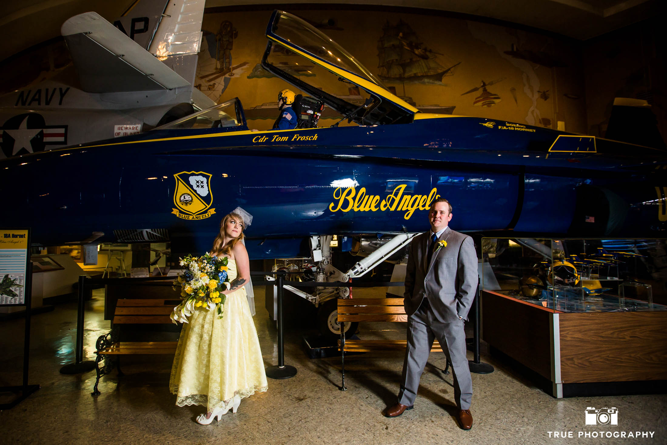 Bride and Groom stand in front of Blue Angels airplane at museum on wedding day