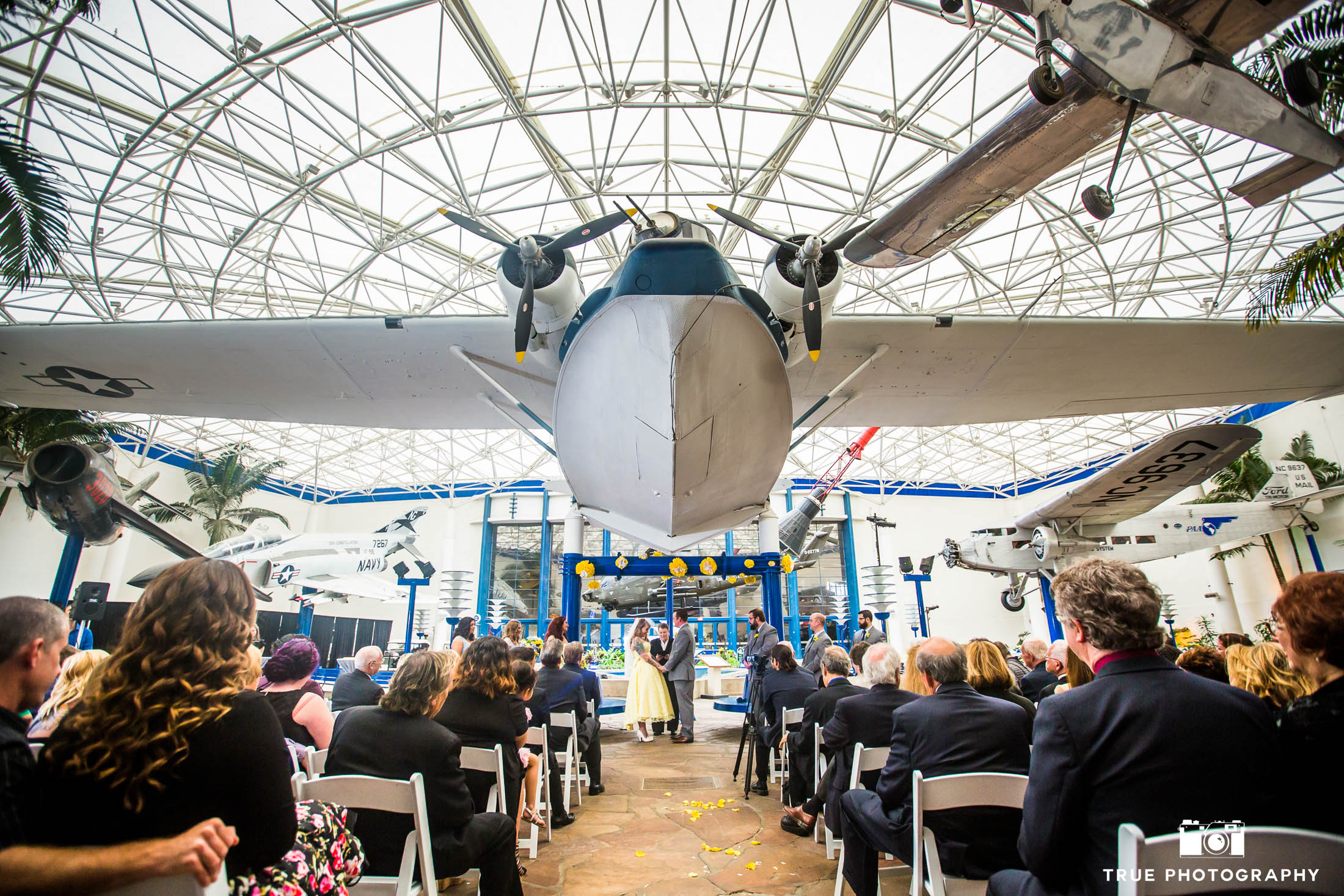 Bride and Groom hold hands under big airplane during Star Wars themed wedding ceremony at museum