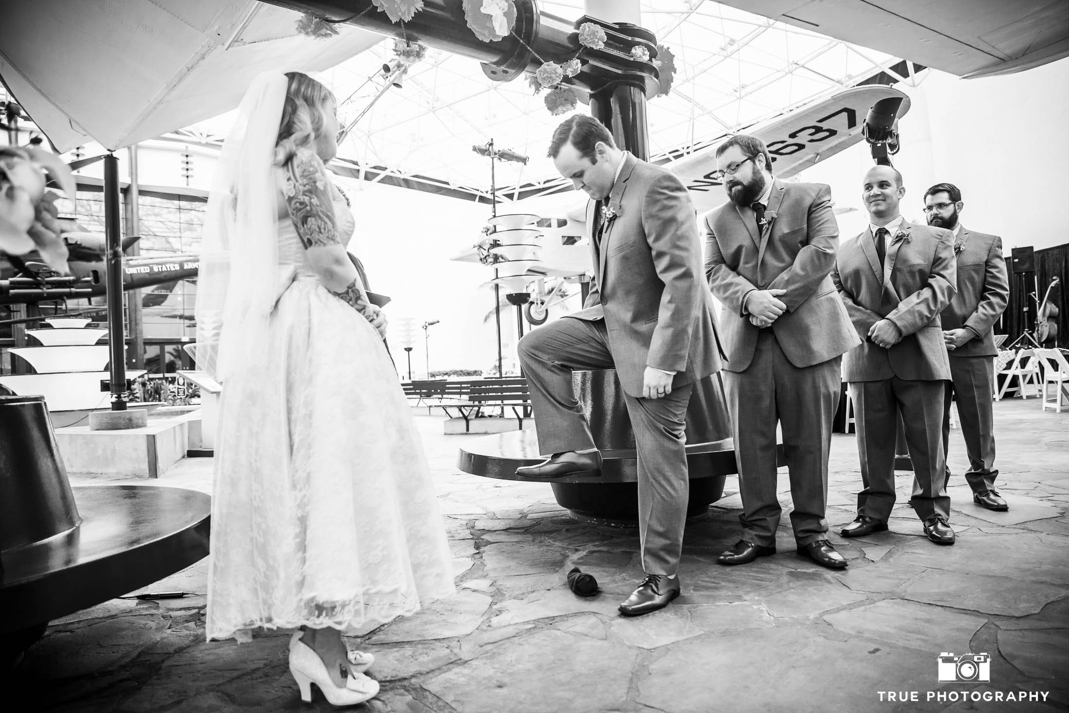 Bride watches as Groom steps on wine glass during wedding ceremony at museum