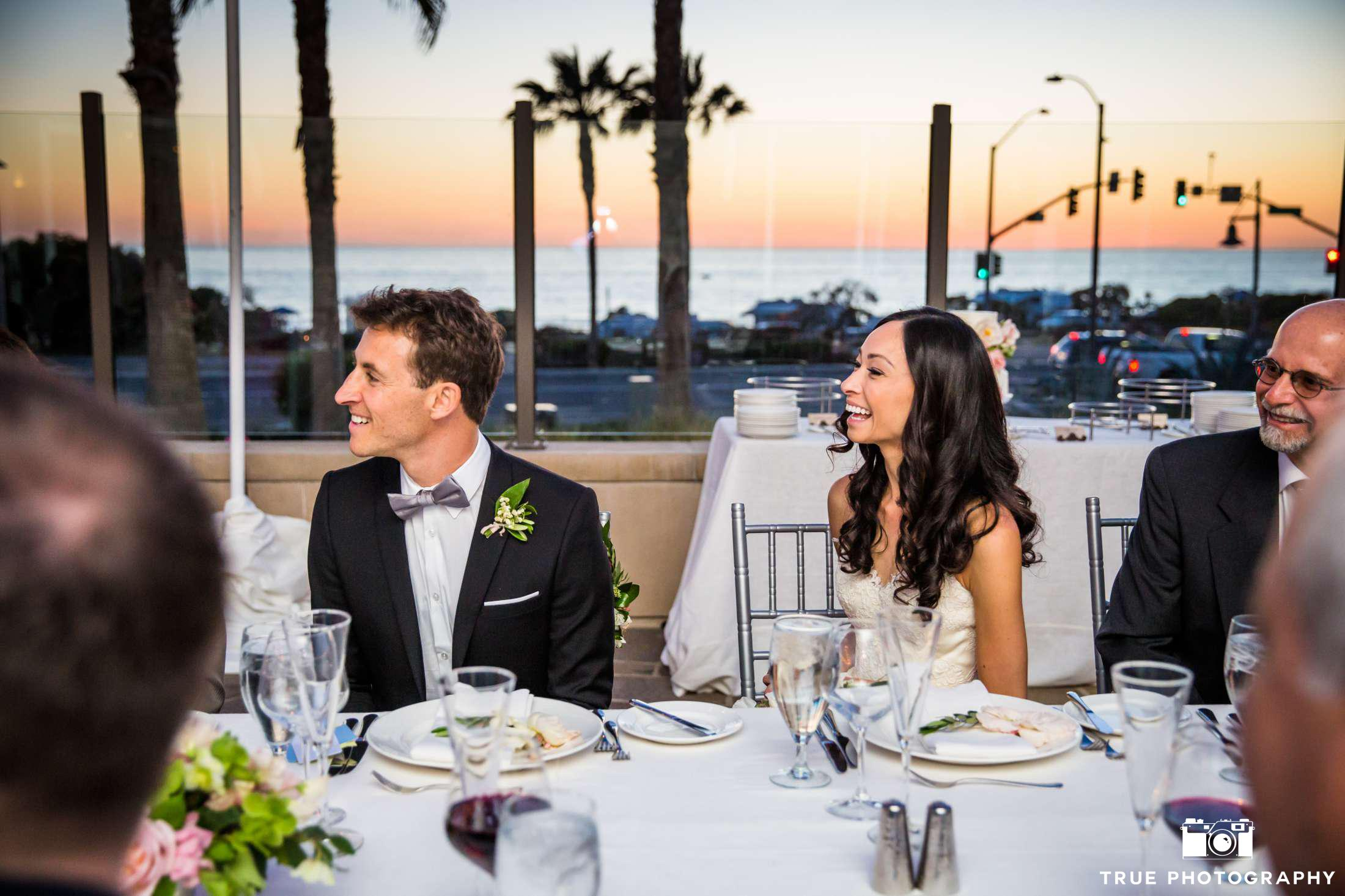 Cape Rey Carlsbad wedding couple at dinner reception table overlooking the ocean