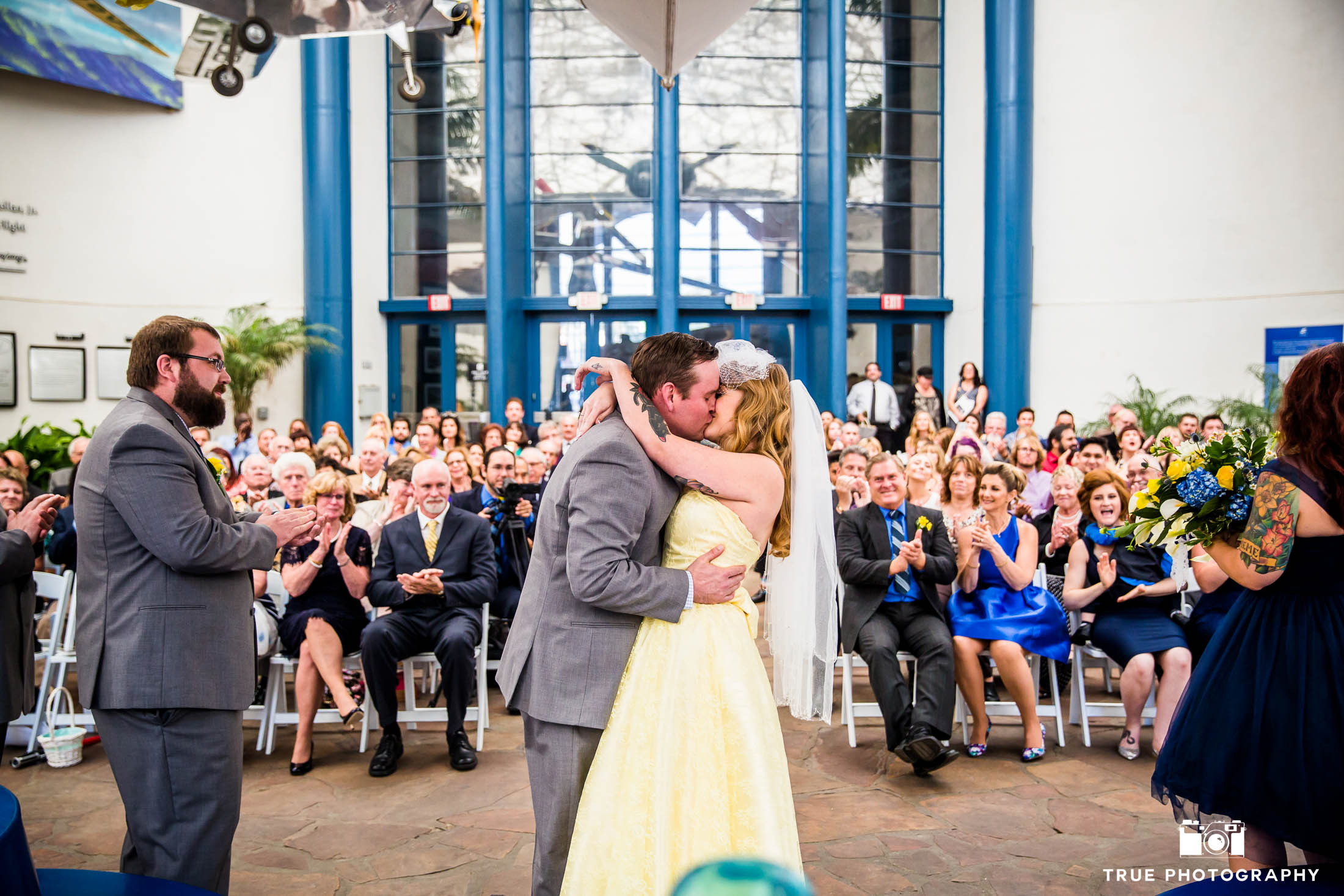 Bride and Groom's First Kiss during wedding ceremony in museum