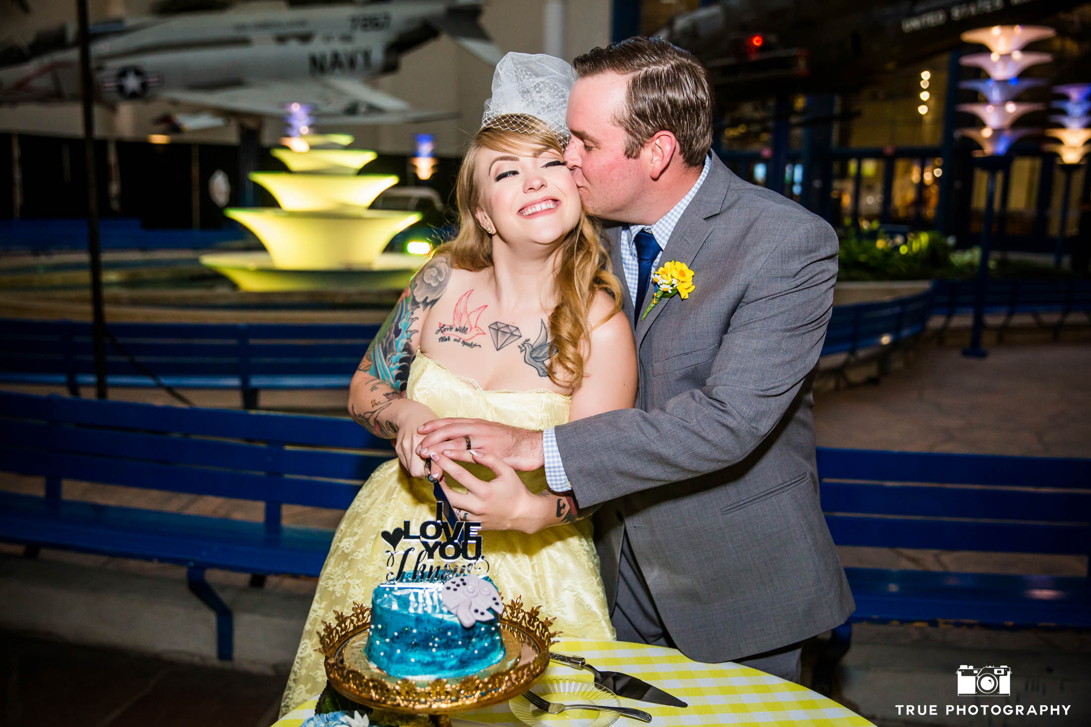 Groom kisses Bride as they cut wedding cake during reception