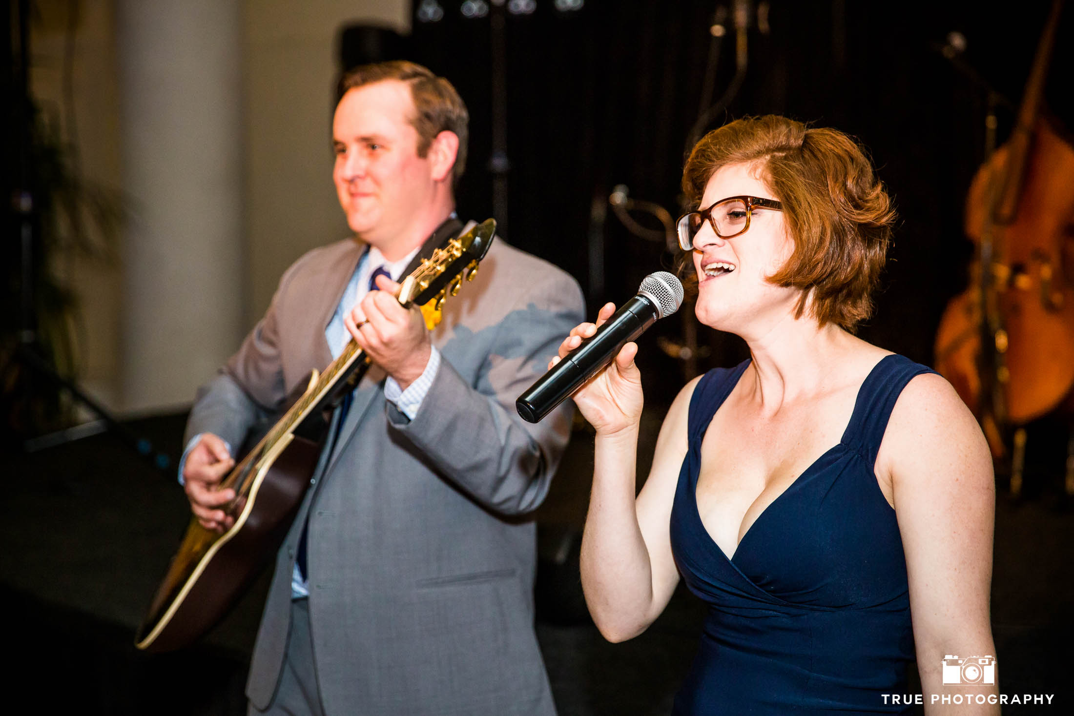 Groom plays guitar and performs with guest during Star Wars themed wedding reception