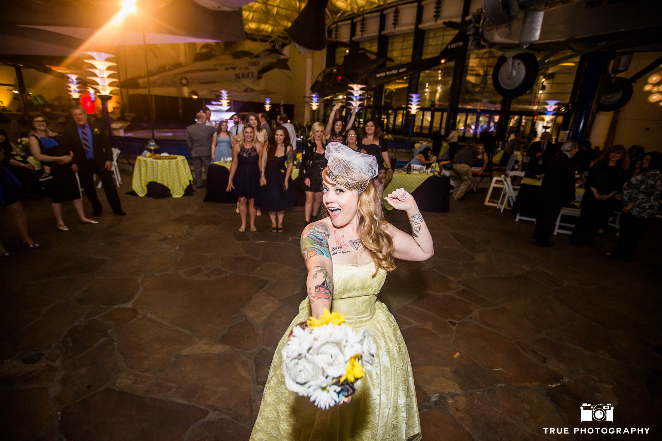 Bride holds out flowers for bouquet toss