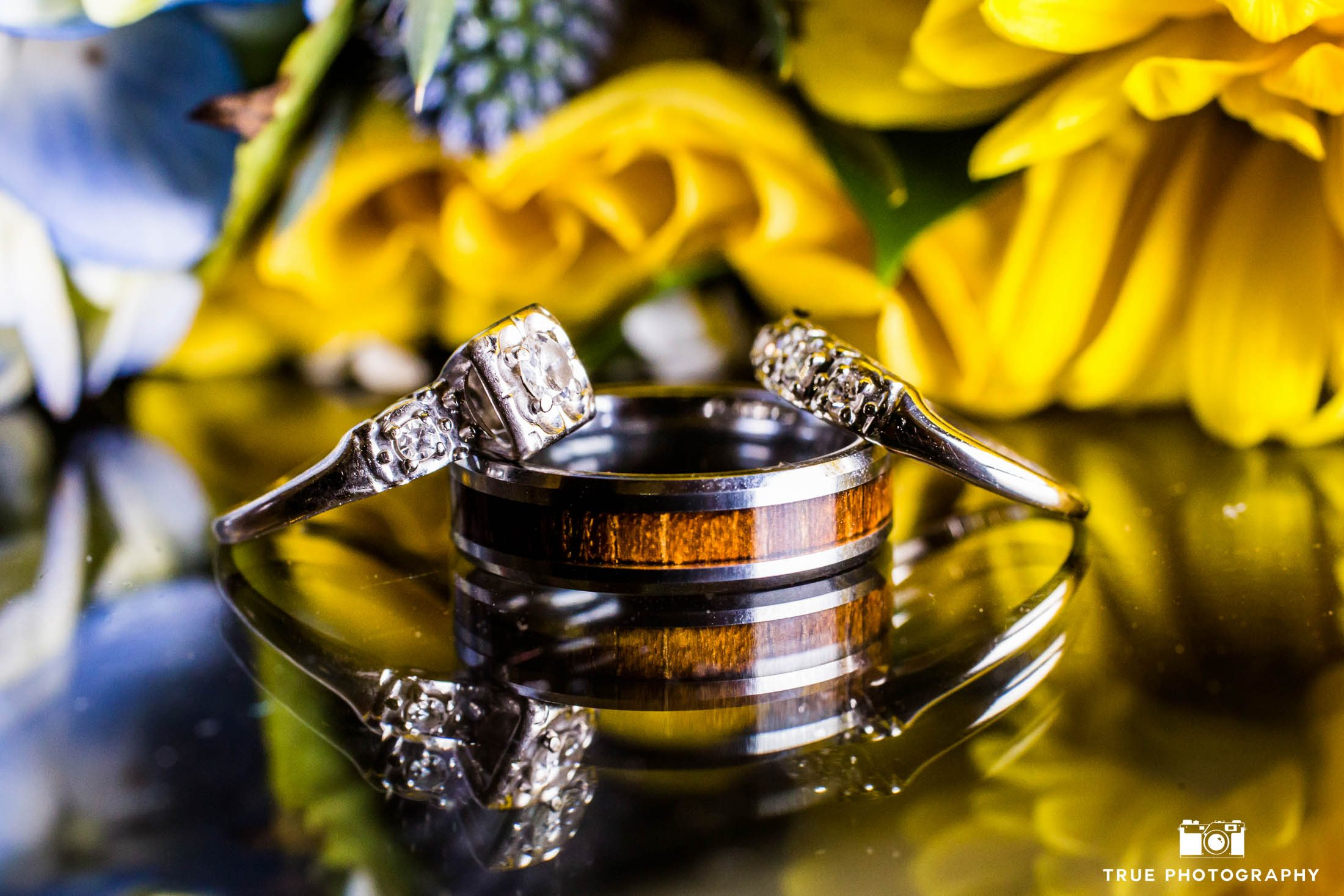 Wedding Rings in front of yellow and blue bouquet of flowers
