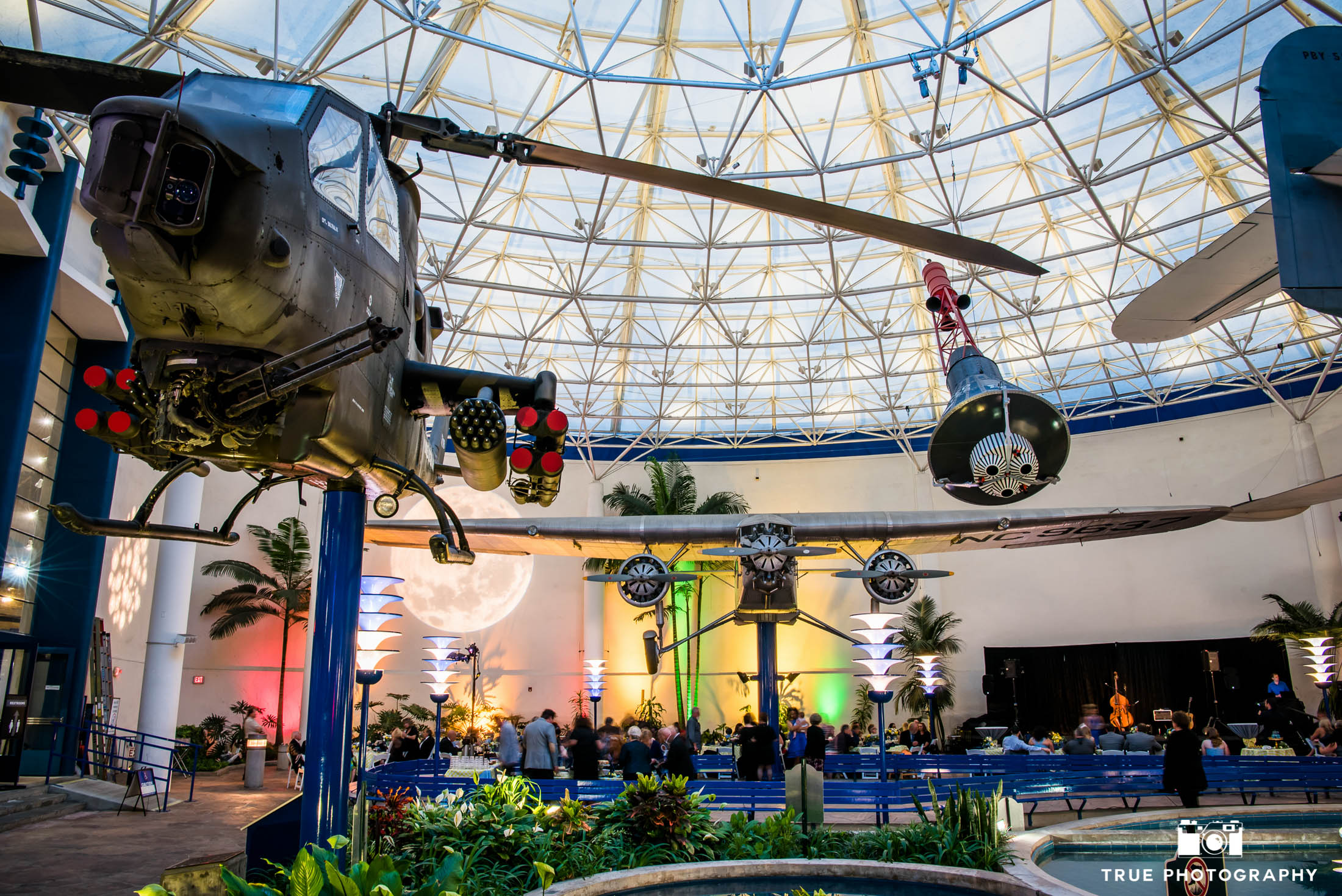 Overall view of wedding reception with colorful uplighting at Plane Museum