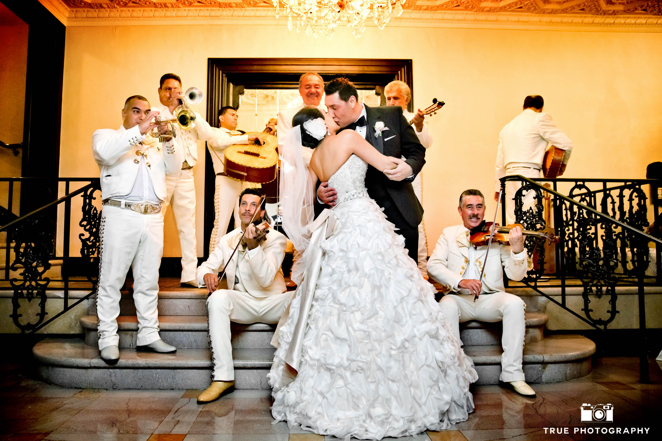 Bride and Groom kiss as mariachi band plays behind them