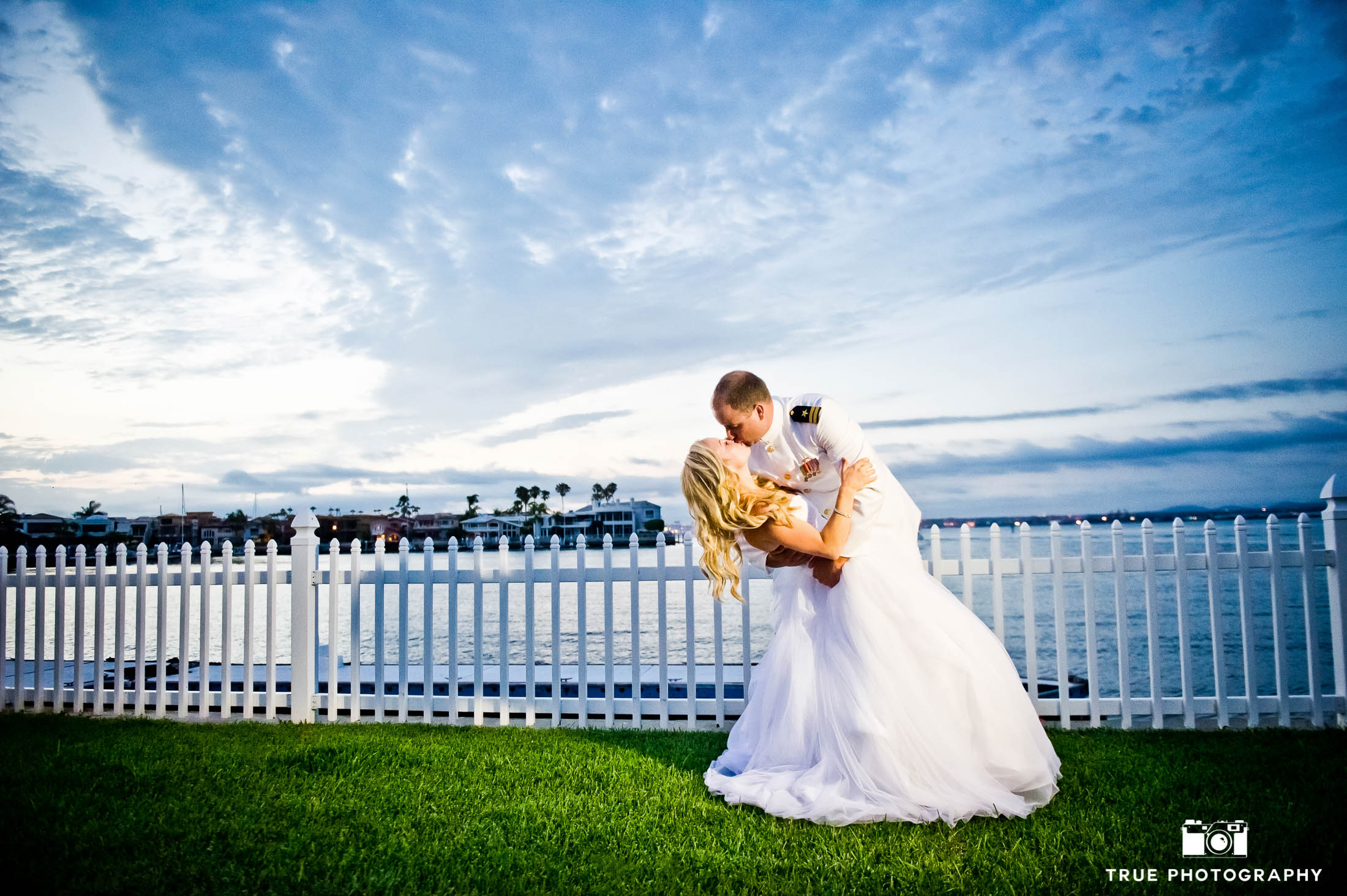 Bride and Military Groom dip for kiss in front of white fence and beach after wedding in Coronado, California