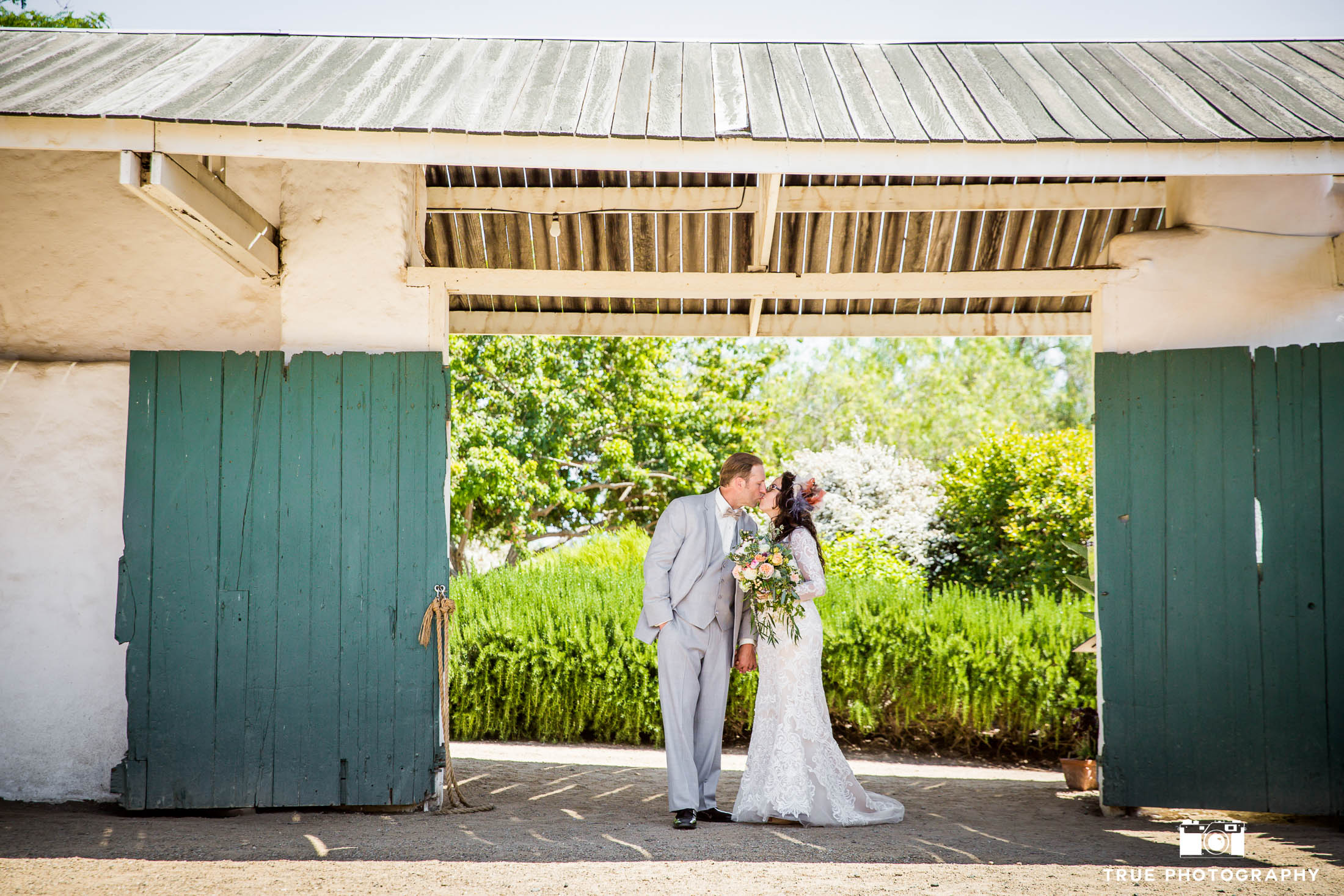 Bride and Groom kiss under Spanish-style Arch with flowers in background