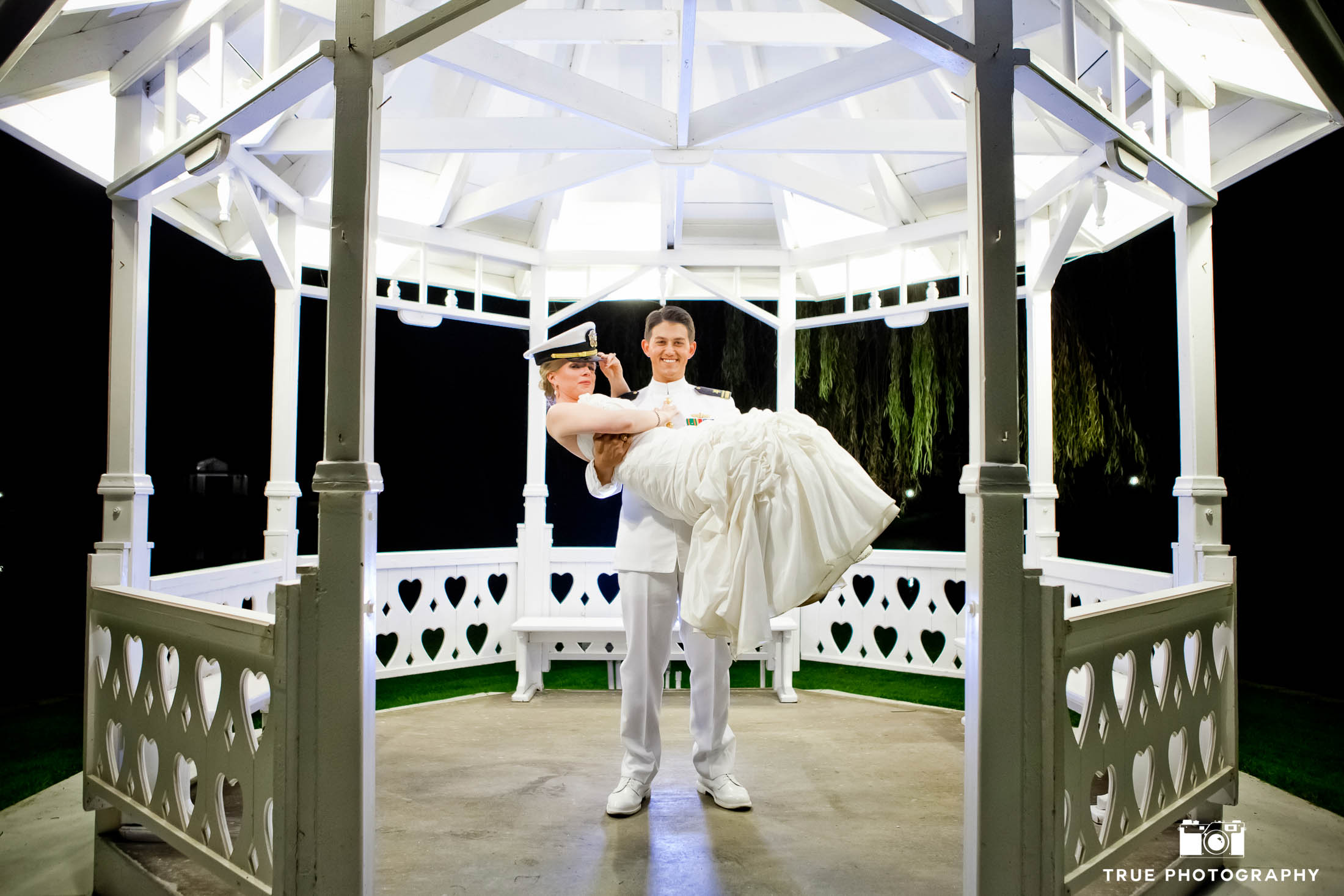 Military Groom picks up Bride for fun wedding couple portrait under white gazebo