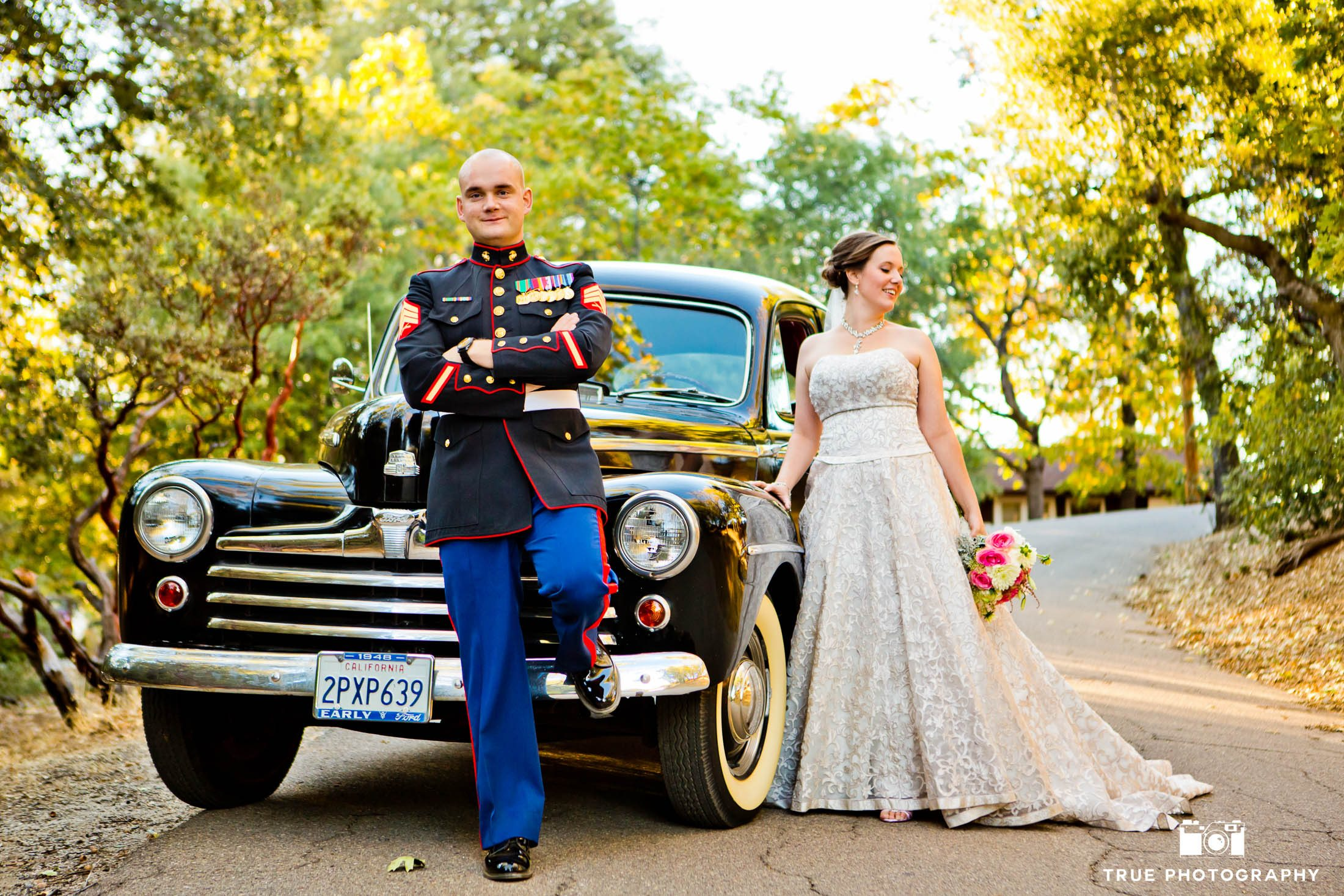 Military Groom and Bride pose with classic Ford car after wedding in Julian, California