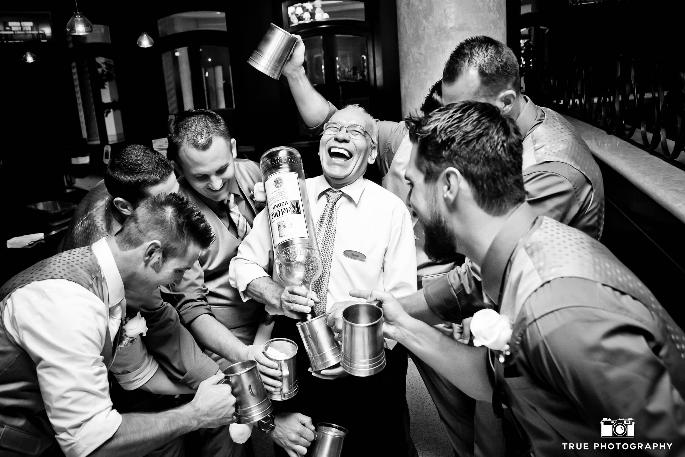 Funny, candid moment of Groomsmen with Dad drinking big bottle of liquor at wedding reception