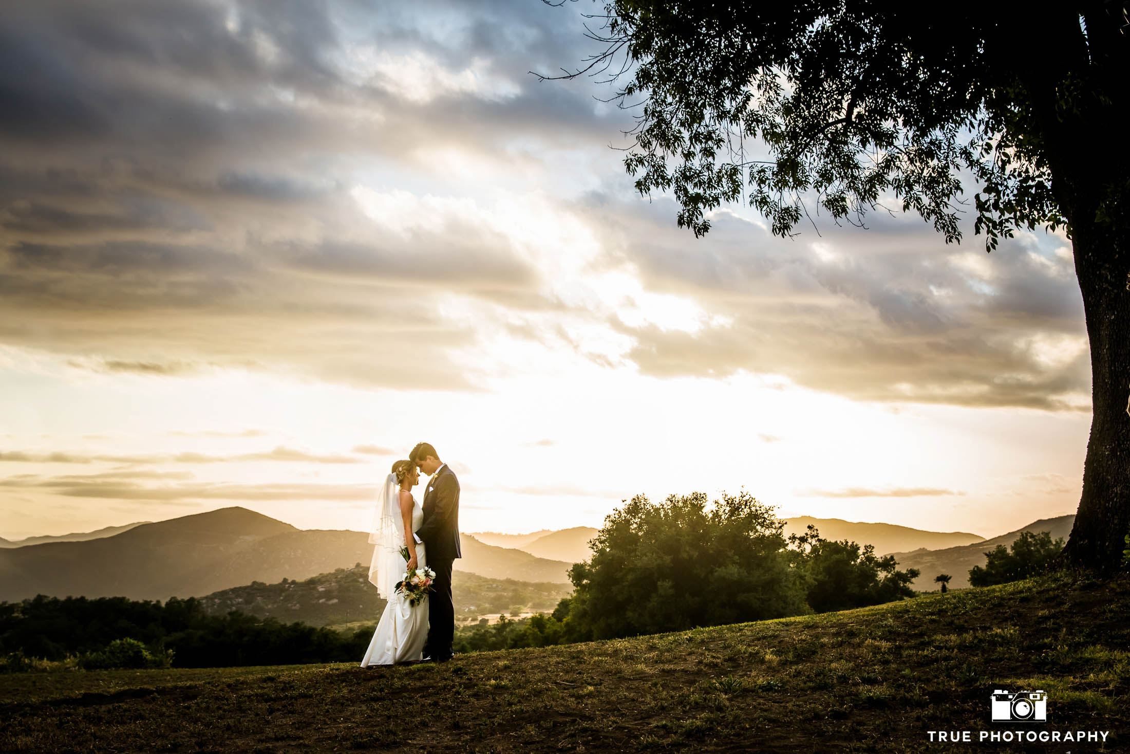 Bride and Groom embrace one another after rustic outdoor wedding ceremony during beautiful california sunset on ranch