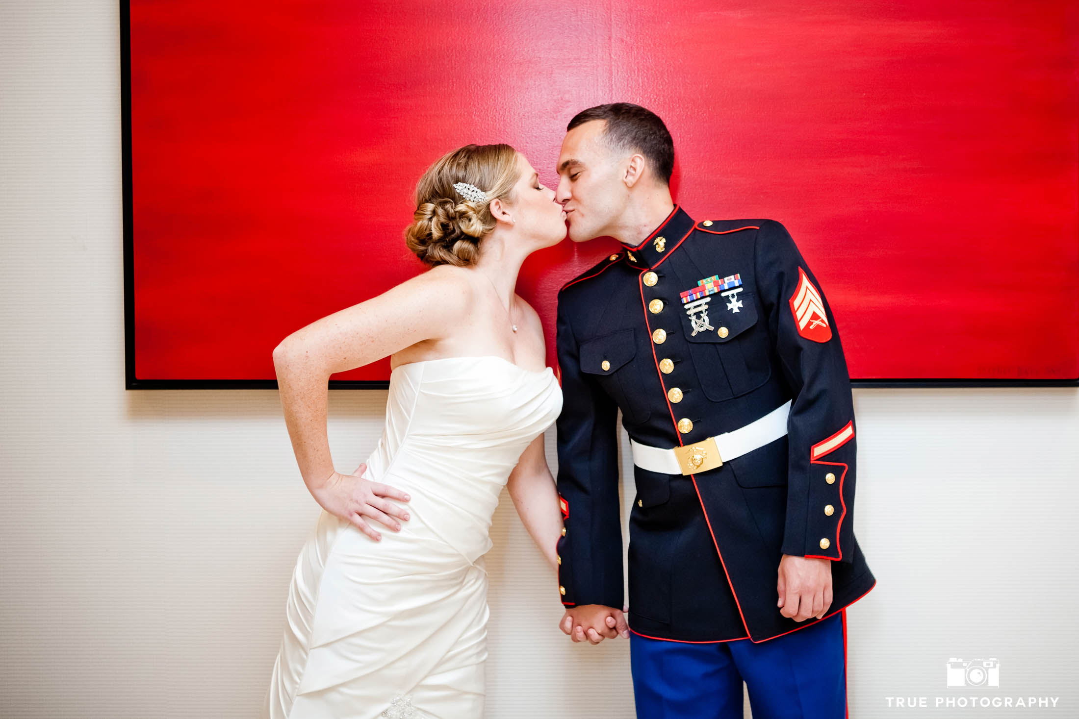 Military Groom and Bride hold hands and lean in for kiss by red painting