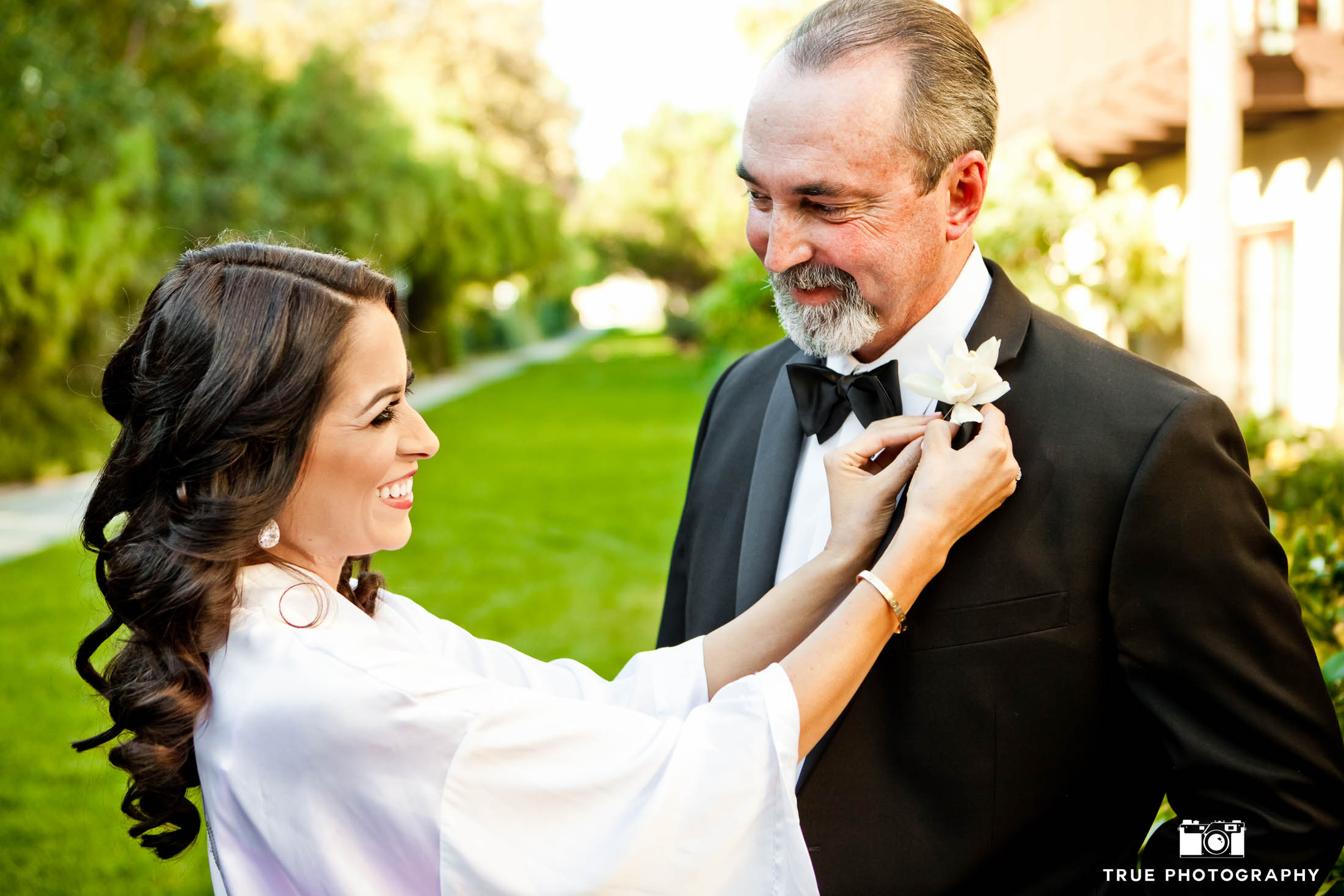 Cute moment with Bride looking at Dad as she puts on his boutonniere