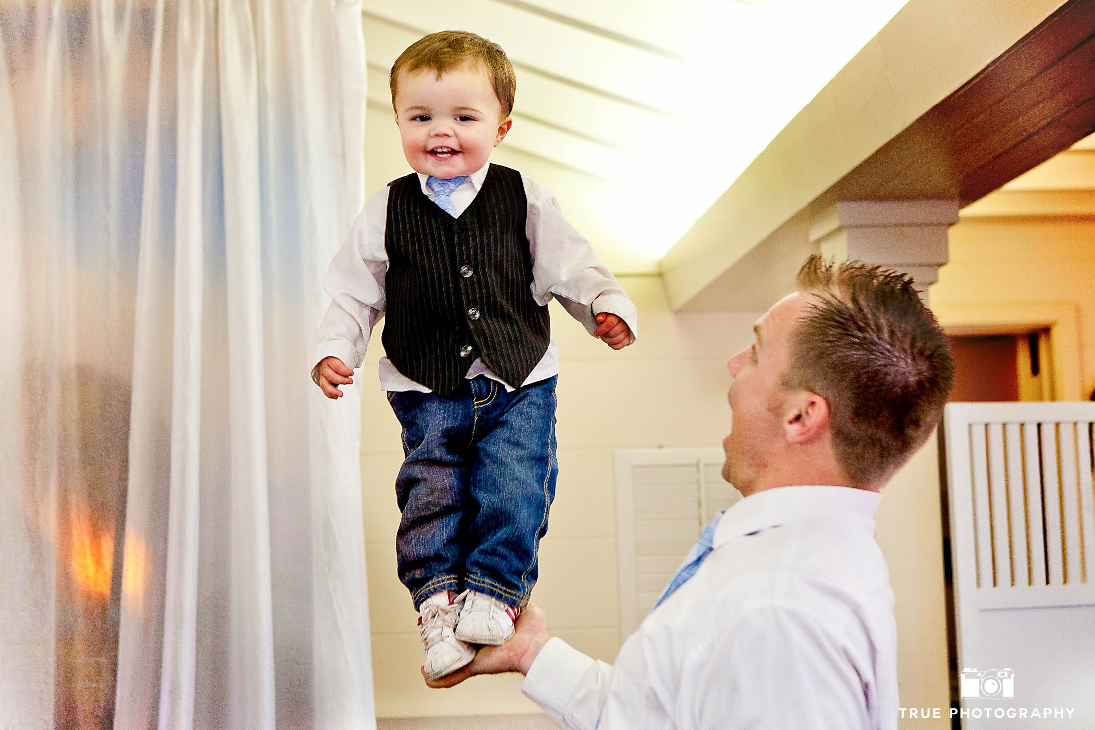Funny photo of Groom holding baby with one hand