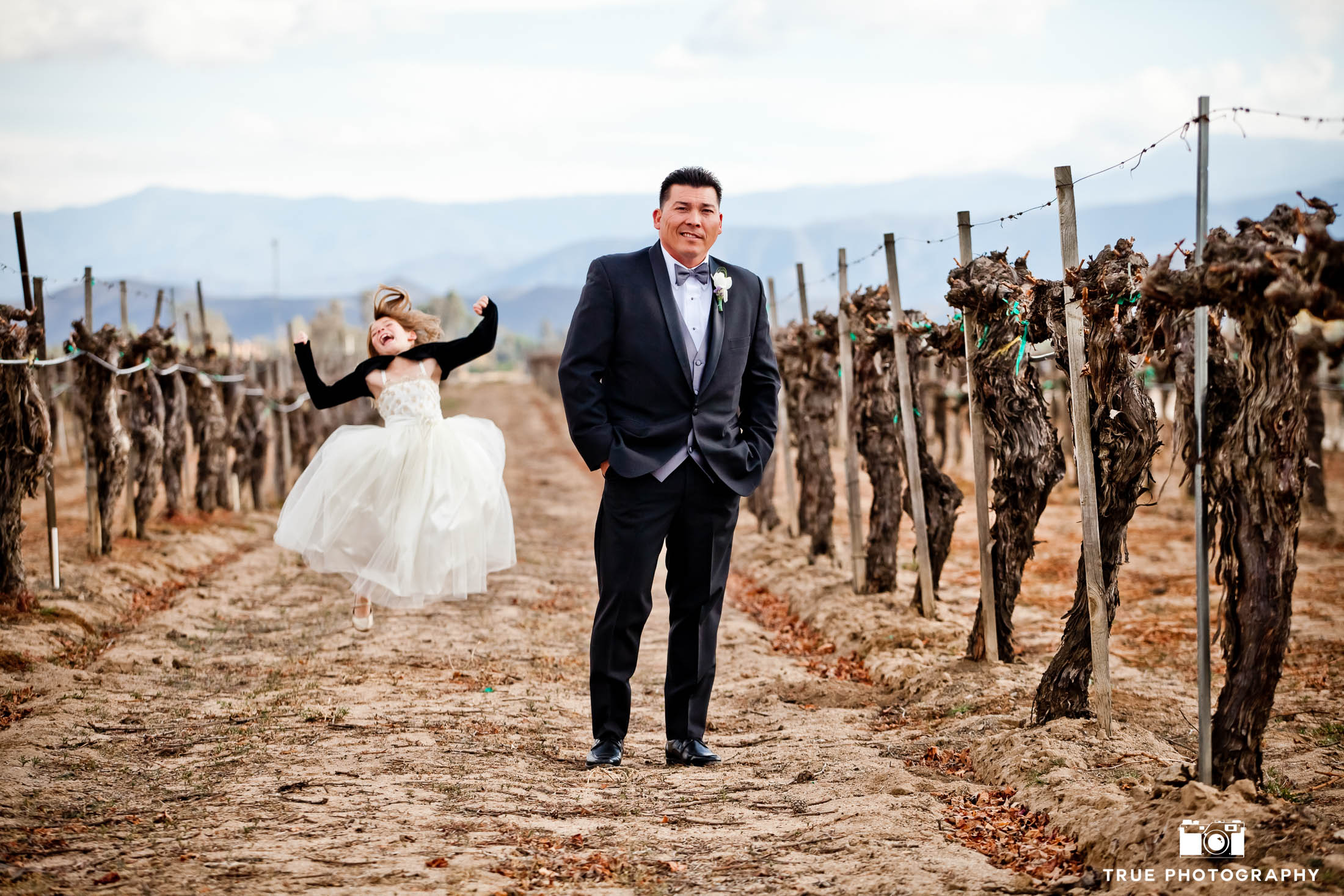 Groom standing in vineyard poses while daughter jumps in background